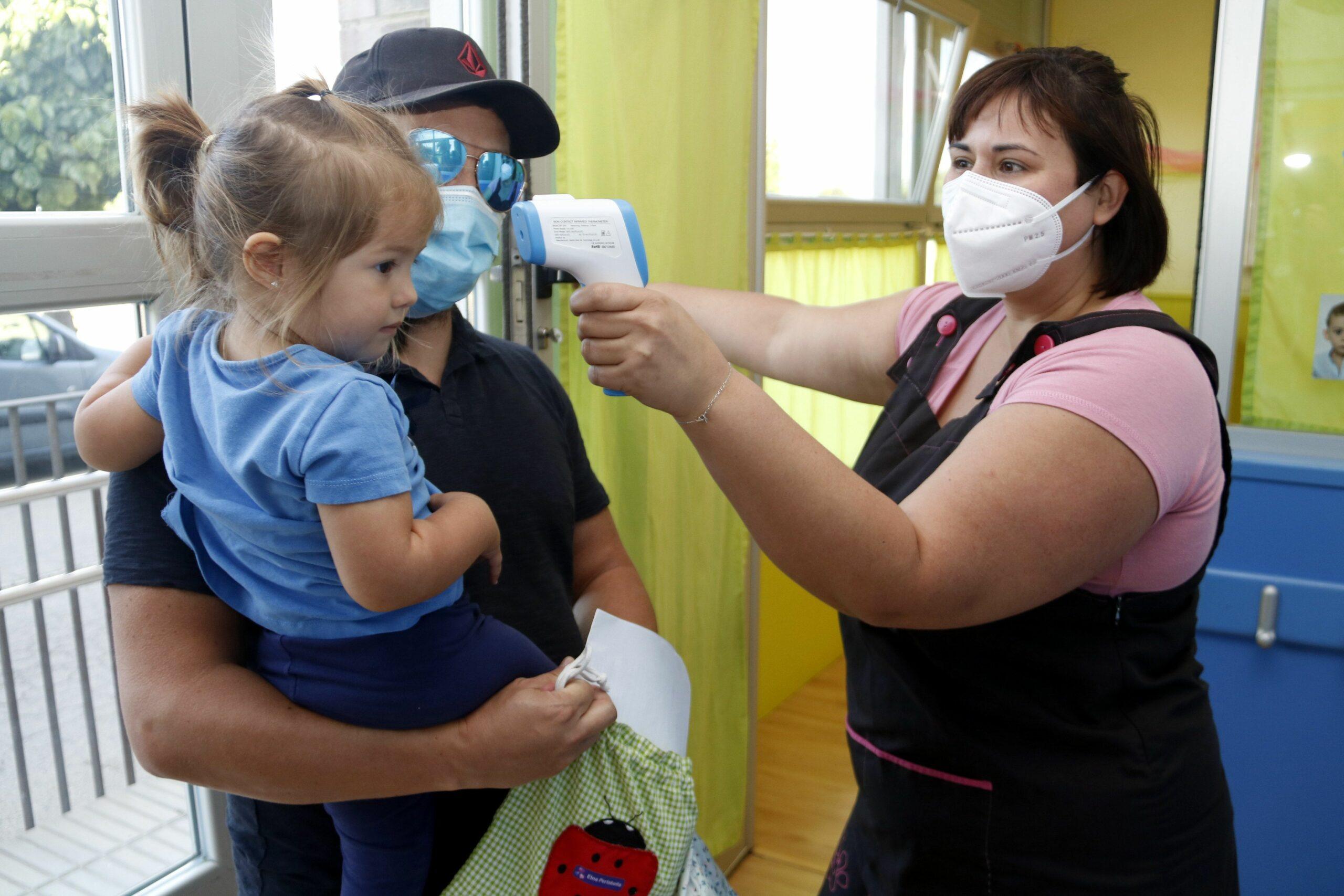 Una professora de l'Escola Bressol de Golmés mesurant la temperatura a una nena que acaba d'arribar al centre