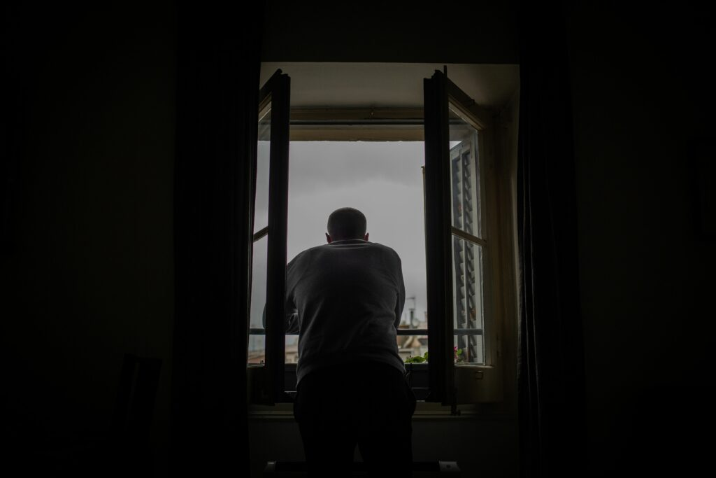 Un home mira per la finestra durant un dia de confinament a Barcelona