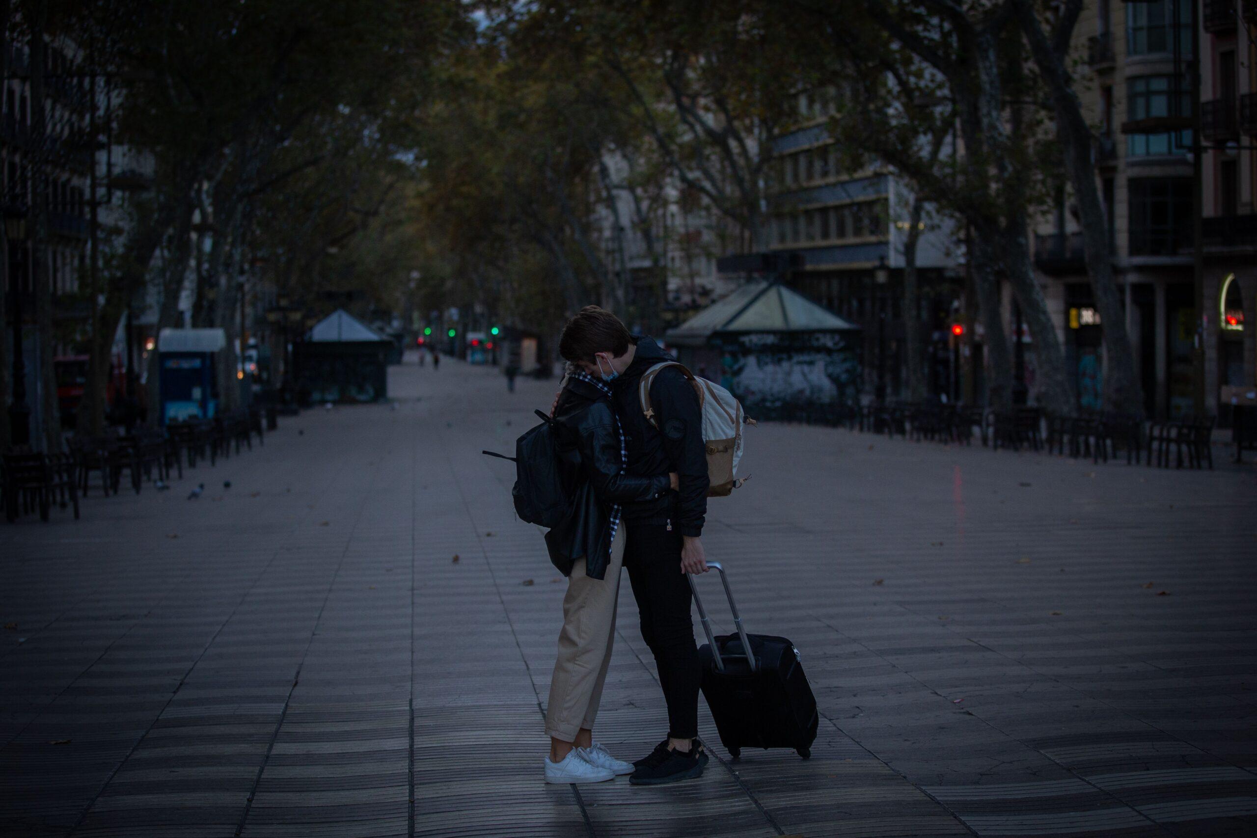 Dos viatgers s'acomiaden pocs minuts després del primer toc de queda al centre de Barcelona / Europa Press