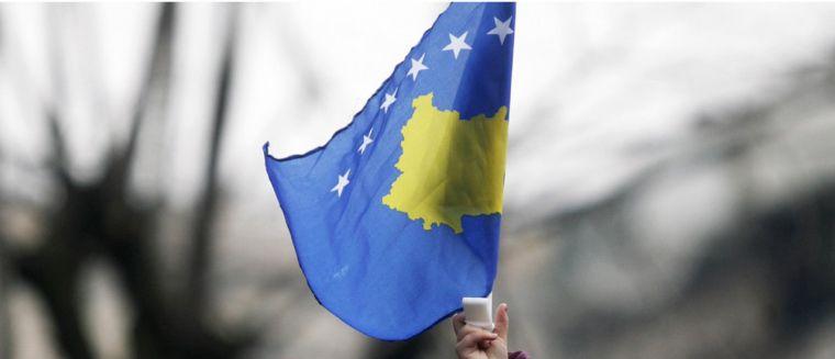 Una nena oneja la bandera de Kosovo a Prístina