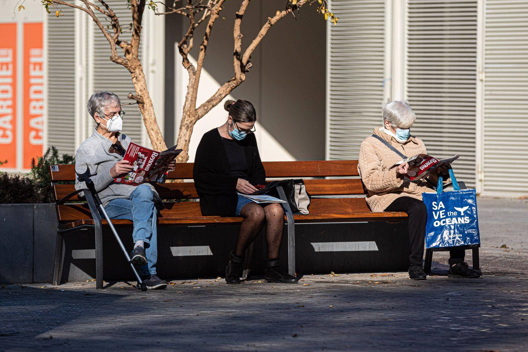 Tres dones amb mascareta assegudes en un banc mantenint les distàncies / Jordi Borràs