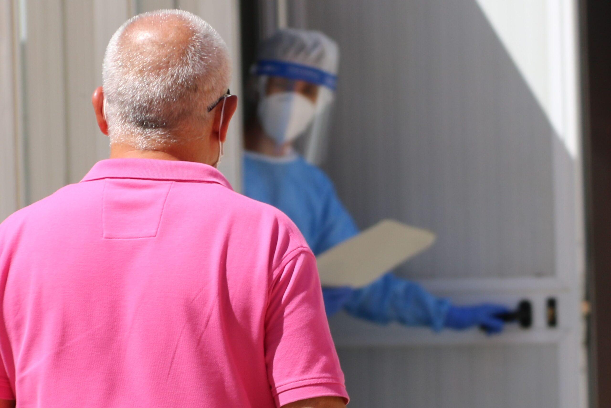 Un home d'esquena, dirigint-se a un mòdul habilitat al CAP Sant Pere de Reus on l'espera una sanitària per fer-li la prova PCR