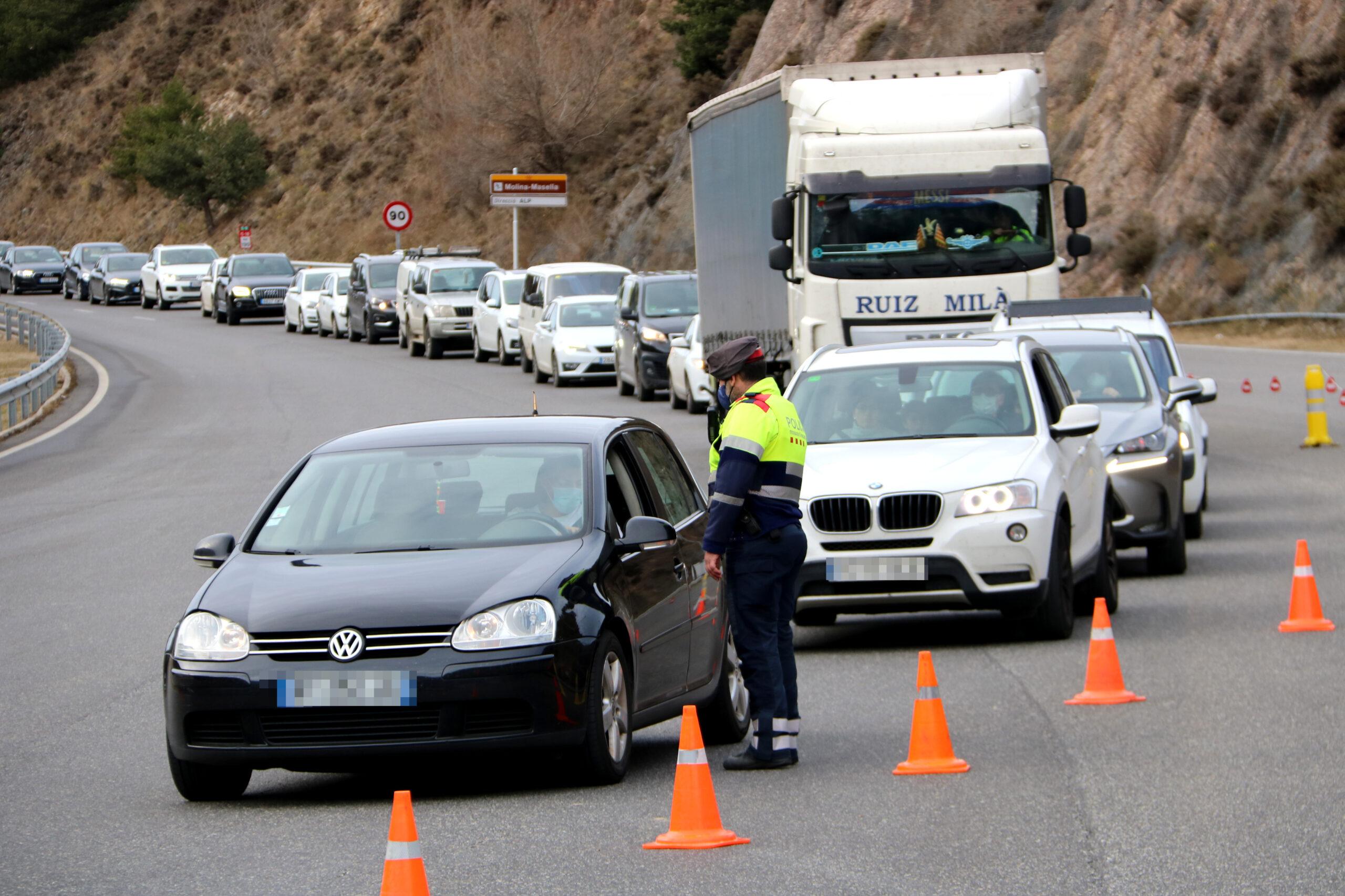 Un mosso parant un dels vehicles que accedien al túnel del Cadí (C-16) en direcció sud i la cua de cotxes al darrere | ACN