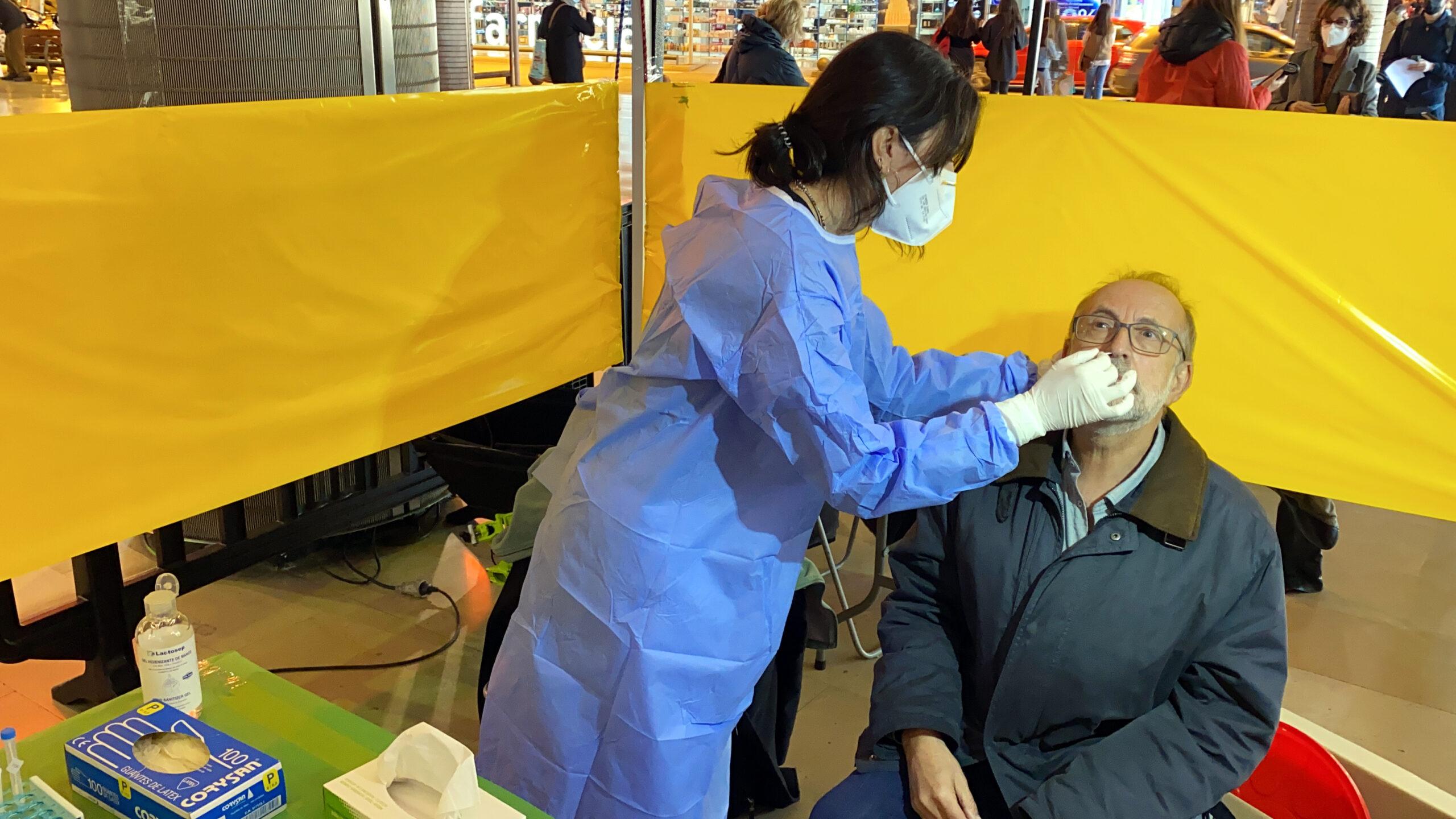 Una persona fent un test ràpid d'antígens en un dels punts de cribratge de la Cambra de Comerç de Barcelona | ACN