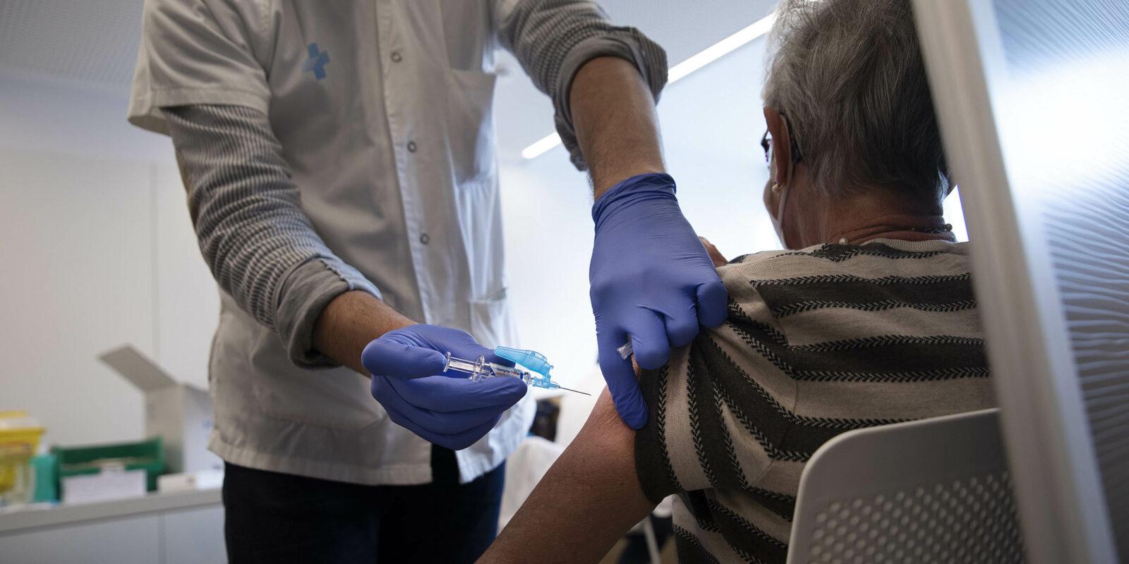 Un metge vacuna una senyora / Jordi Play