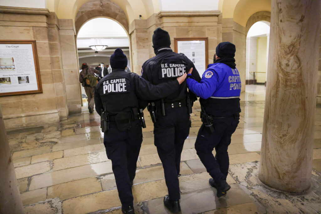 Membres de la policia del Capitoli caminen dins l'edifici mentre els manifestants protesten a l'exterior | Reuters