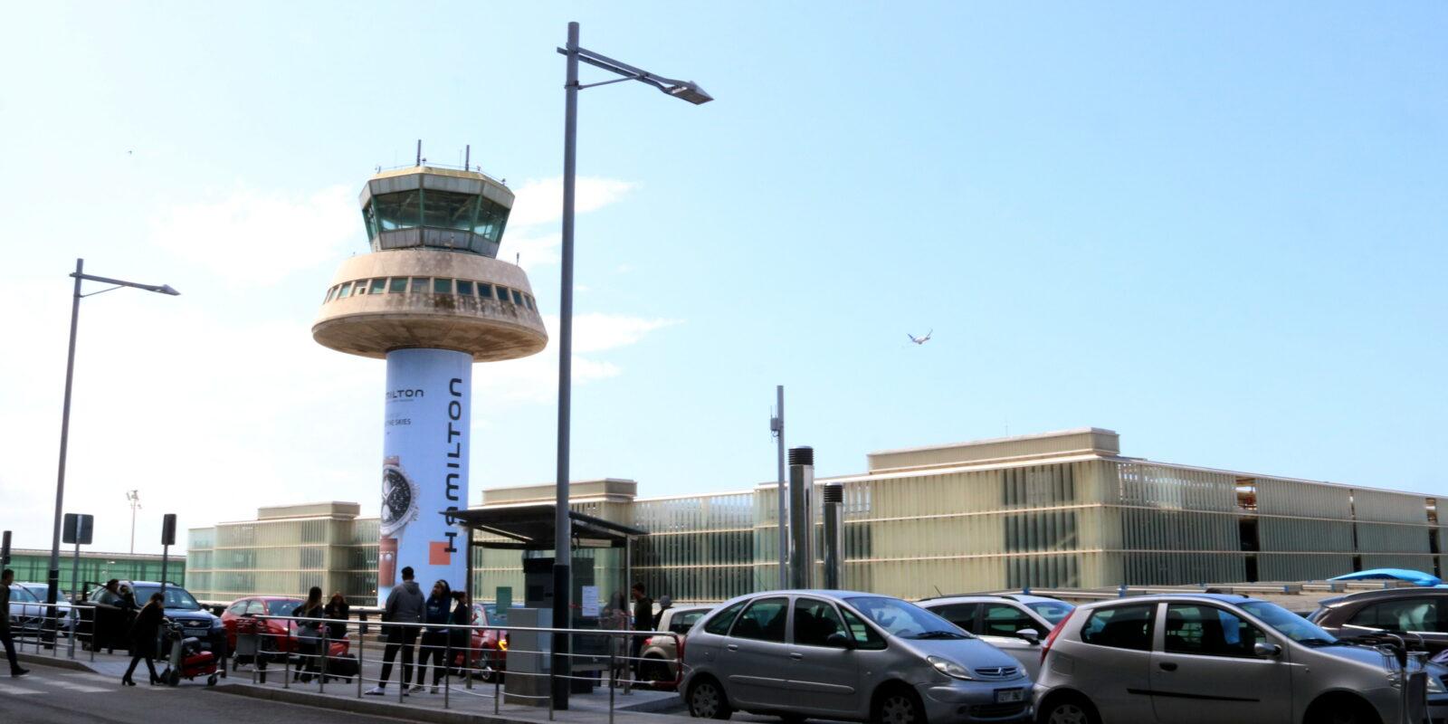 L'entrada de la Terminal T1 de l'aeroport de Barcelona-El Prat, amb l'antiga torre de control al fons i un avió que sobrevola la zona / ACN