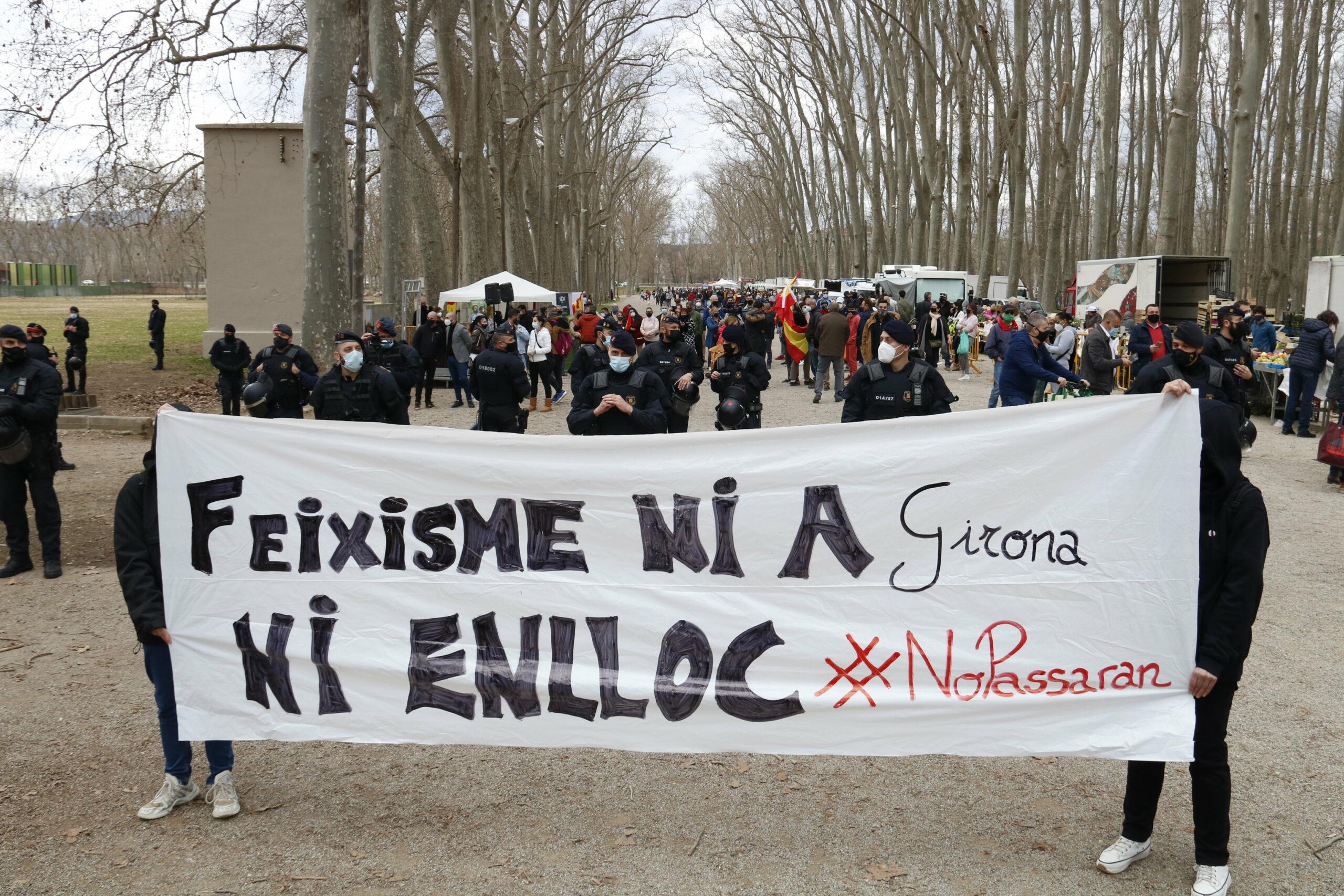 Un grup d'antifeixistes amb un cartell rebutjant la presència de Vox, al Parc de la Devesa de Girona, amb la carpa del partit d'ultradreta al fons, ahir / ACN