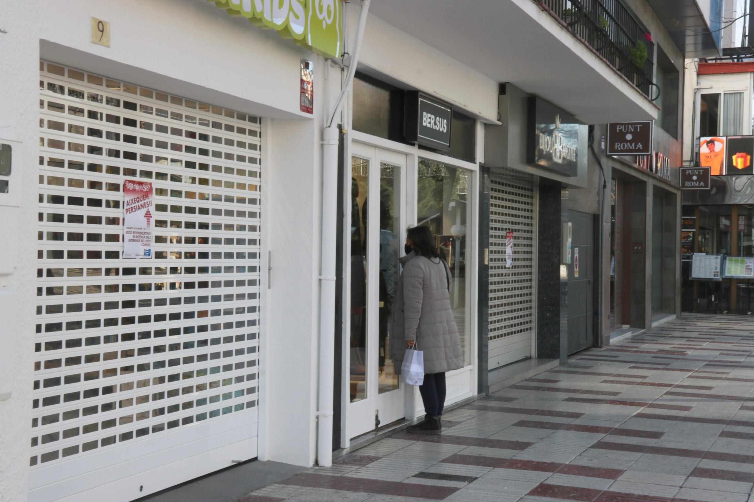Una dona es mira un aparador d'una botiga tancada a Platja d'Aro | ACN