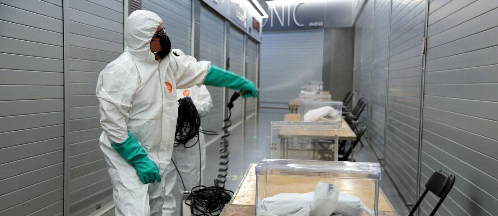 Un operari del dispositiu del 14F muntant una mesa electoral amb totes les mesures de seguretat i mètodes de desinfecció / ACN