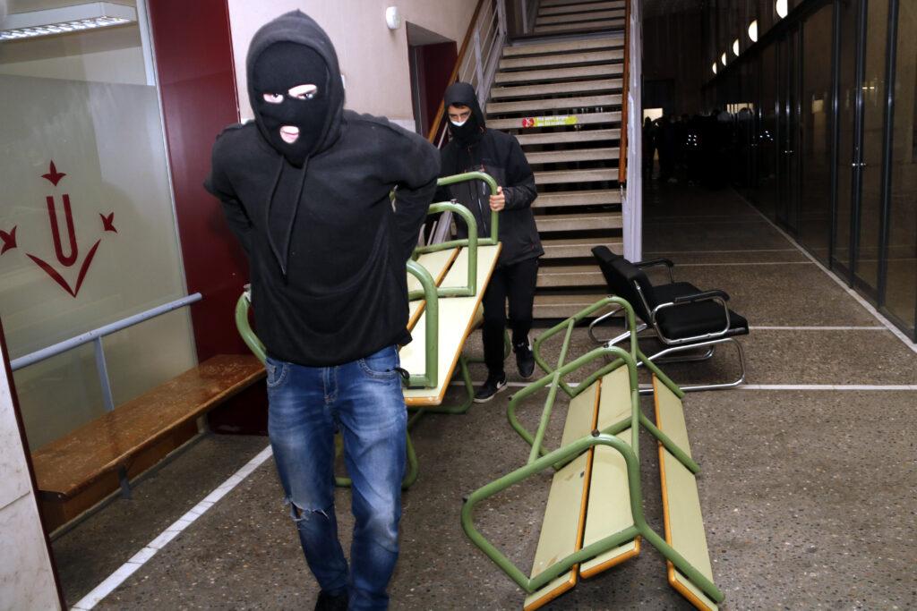 Dos joves encaputxats i amb la cara tapada traslladant un banc per fer barricades i reforçar la tancada a la UdL per Pablo Hasél | ACN