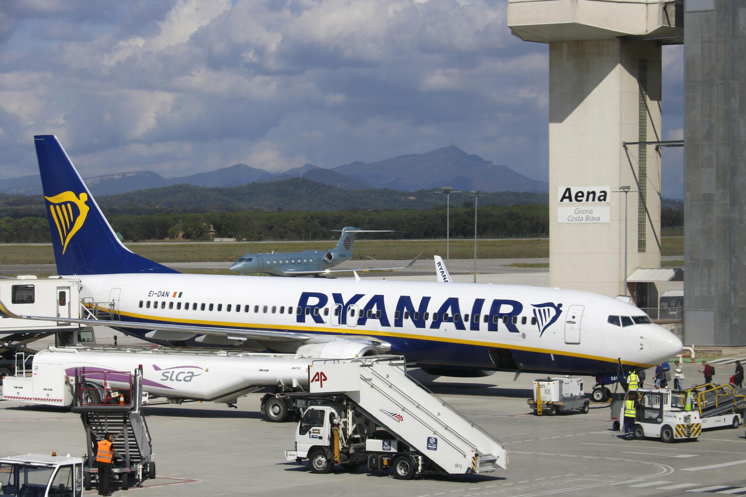 Un dels avions de Ryanair aterrats a l'Aeroport Girona-Costa Brava amb la torre de control de fons | ACN