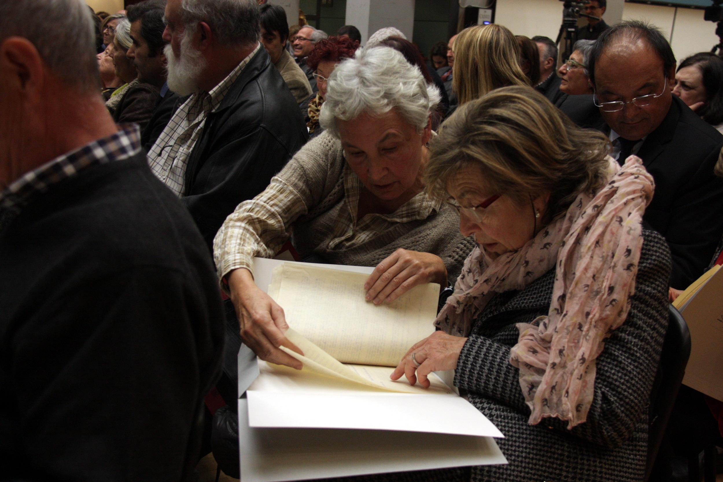 Dues dones revisen els 'papers de Salamanca' recuperats, en l'acte de lliurament del 3 de desembre de 2015   ACN