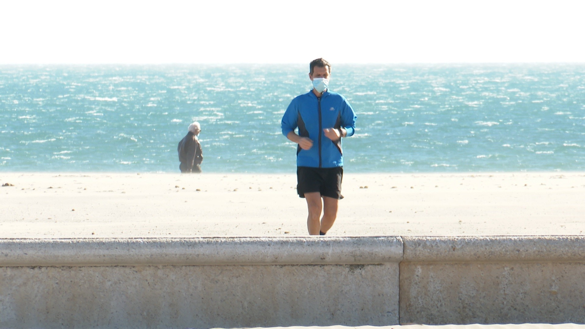 Un home corrent amb mascareta a la platja / EP