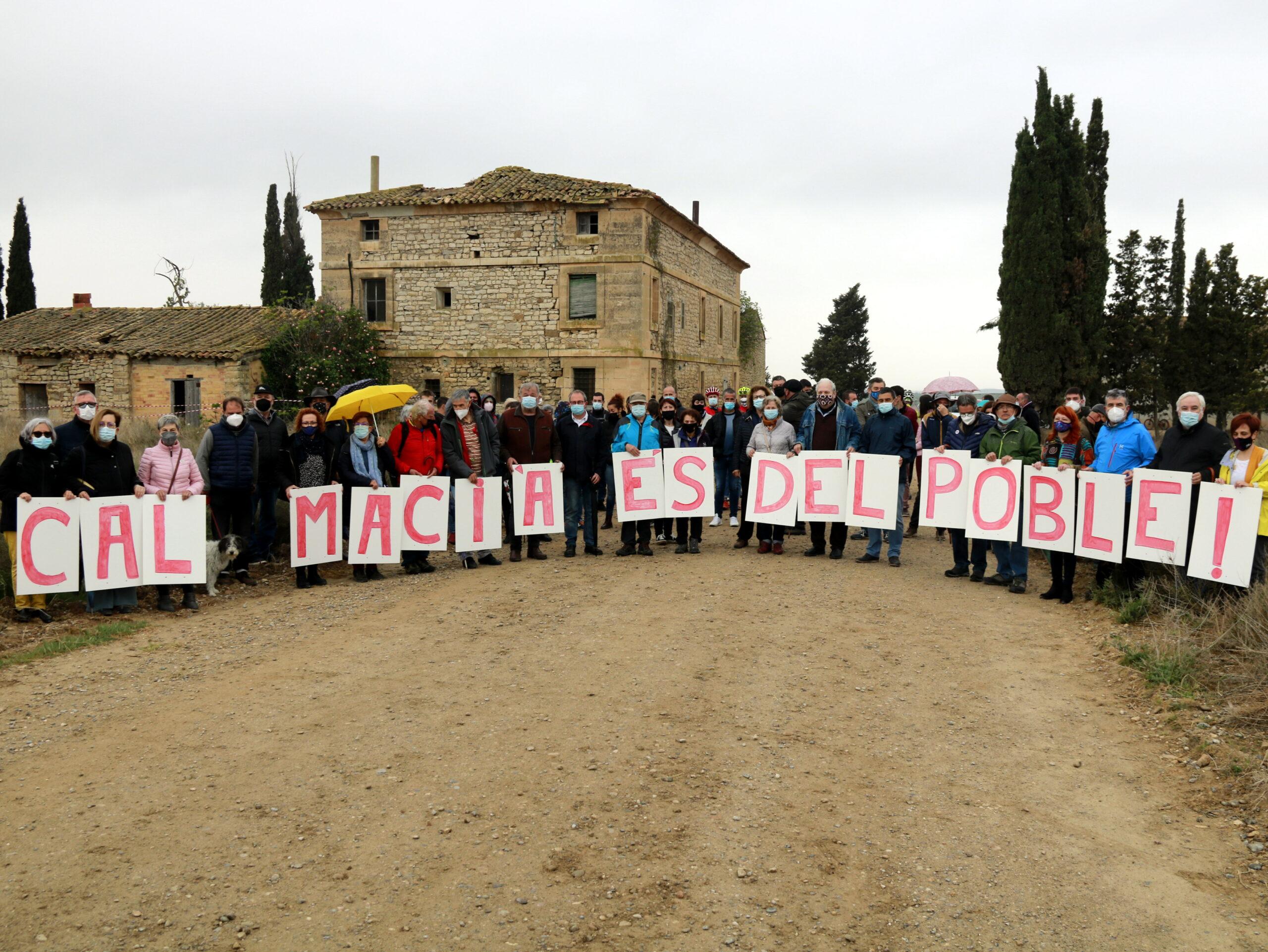 """Alguns dels participats a l'acte Vallmanya amb un cartell que reclama que """"Cal Macià és del poble"""" i la casa al fons (ACN)"""
