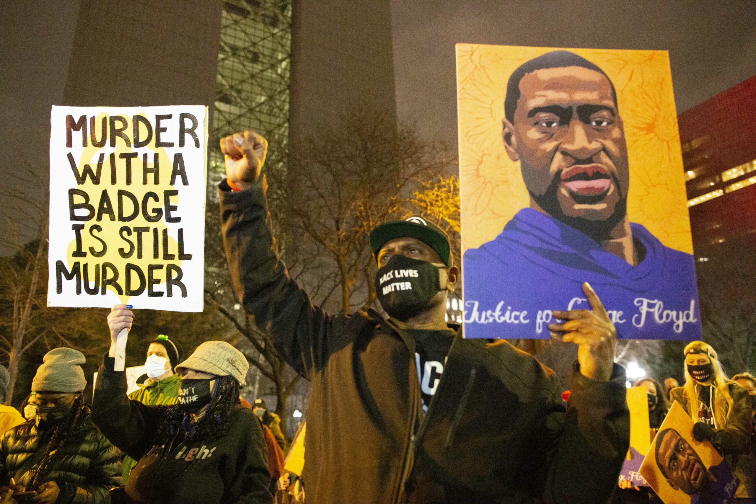 Una home negre subjecta un retrat de George Floyd en una manifestació a Minneapolis | Europa Press