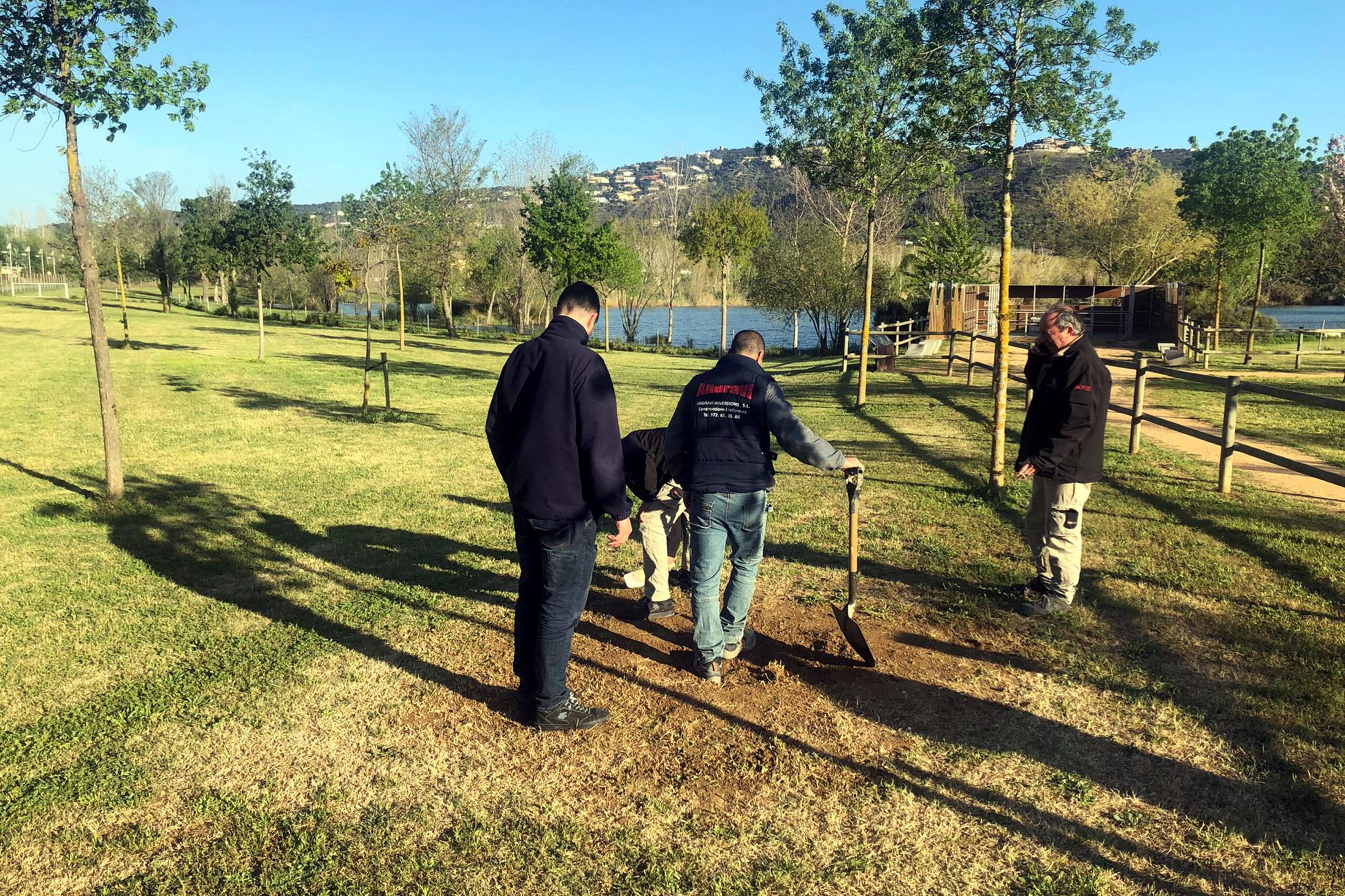 El personal de la brigada al parc dels Estanys, tapant amb terra la base de formigó on hi havia el monòlit d'acer inoxidable | ACN