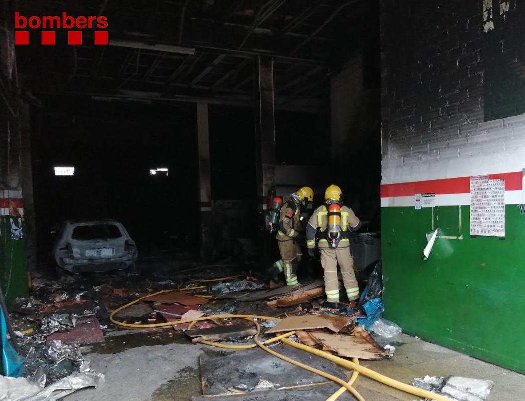 Efectius dels Bombers treballen en l'extinció d'un incendi en un taller mecànic de Manresa el 16 d'abril del 2021. Pla general. (Horitzontal)