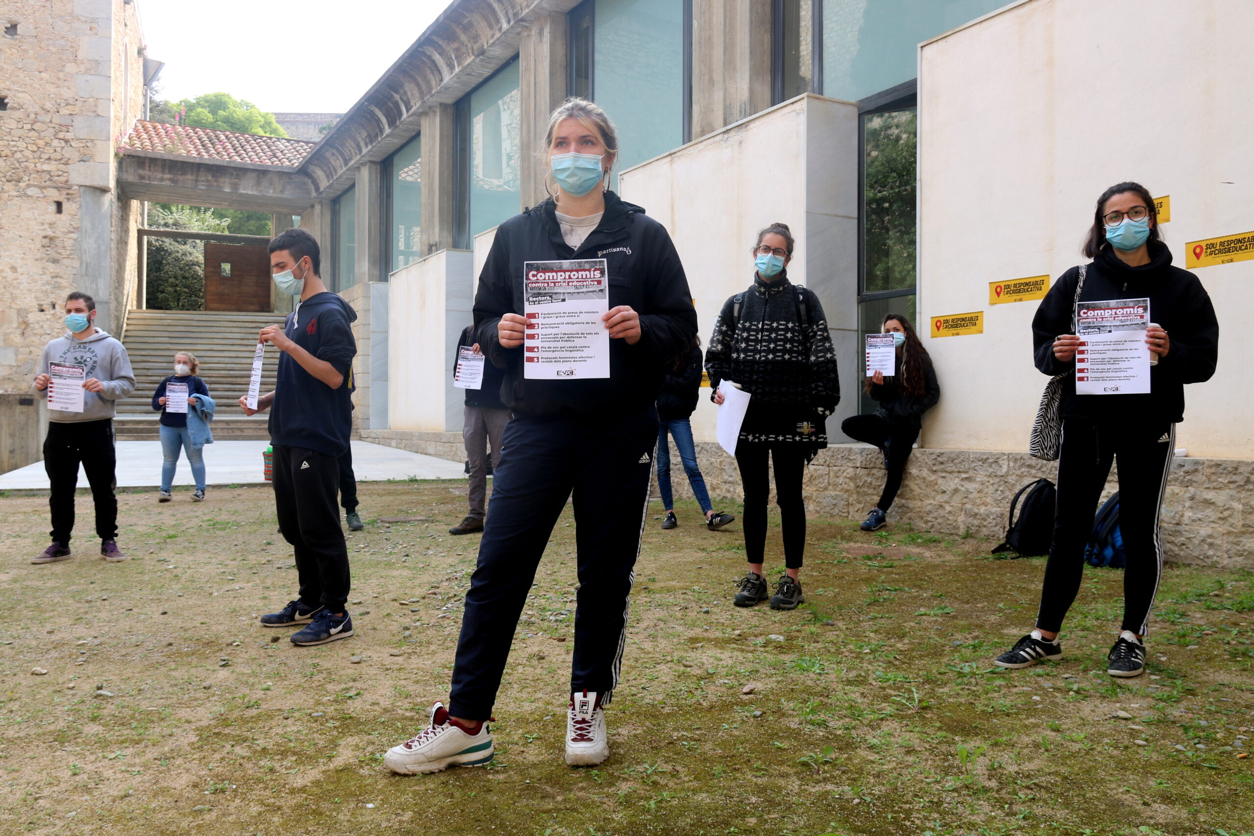 Els estudiants de la UdG al pati del rectorat, amb els cartells reclamant que se signi el compromís contra la crisi educativa | ACN