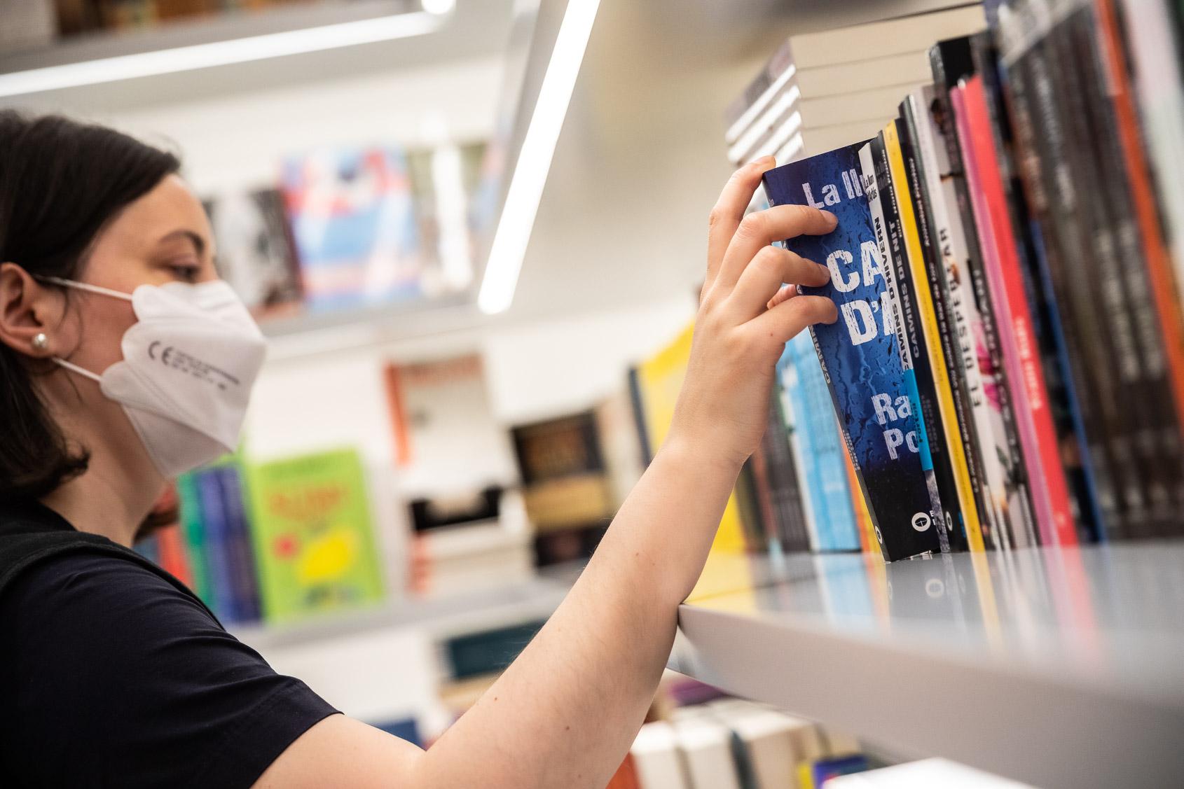 Una treballadora de la llibreria Ona col·locant llibres a la prestatgeria (Jordi Borràs)