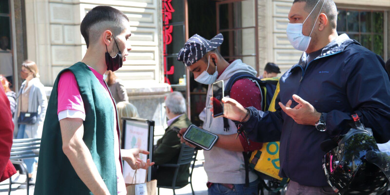 Un treballador de La Casa del Llibre entregant comandes als repartidors de Glovo al Passeig de Gràcia de Barcelona.  (ACN)