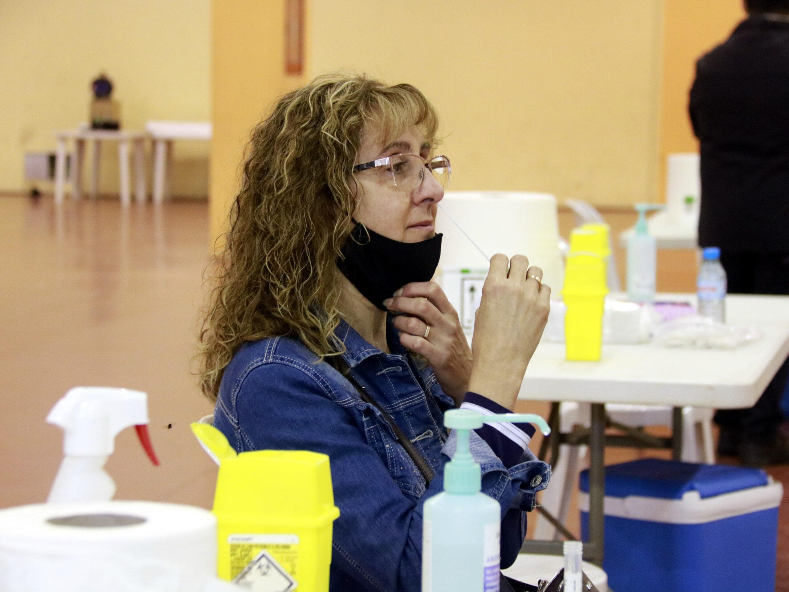 Una dona fent-se la prova PCR d'automostra al Pavelló Firal de Mollerussa | ACN