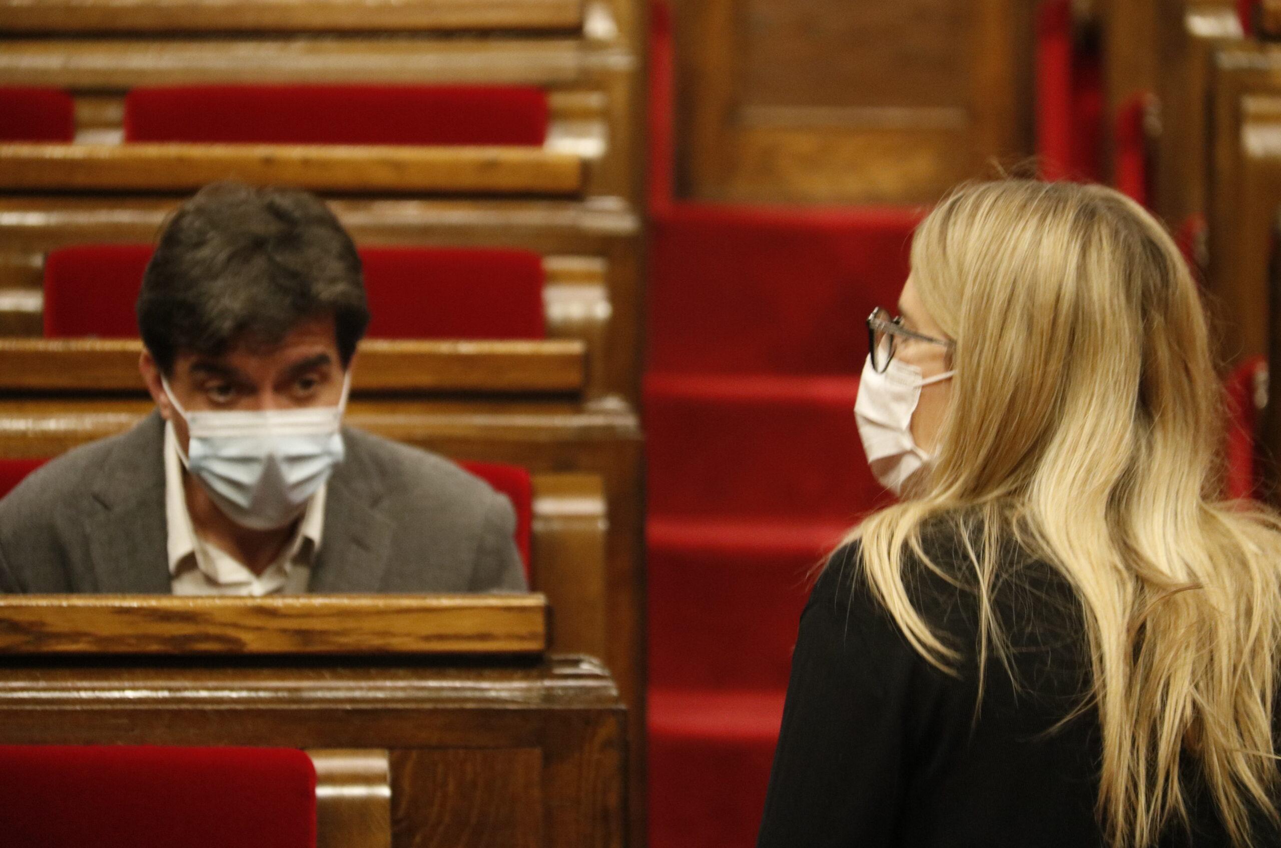 El líder d'ERC al Parlament, Sergi Sabrià, assegut al seu escó del Parlament mentre la diputada i regidora de JxCat Elsa Artadi puja les escales de l'hemicicle | ACN