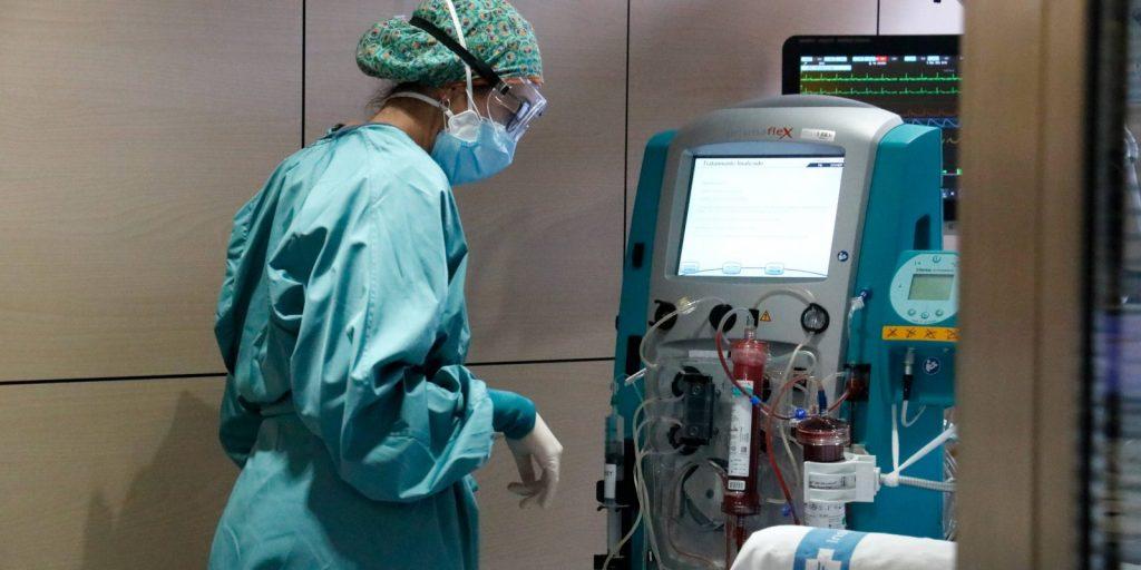 Una infermera mirant-se una màquina que filtra la sang de pacients amb Covid-19 / ACN