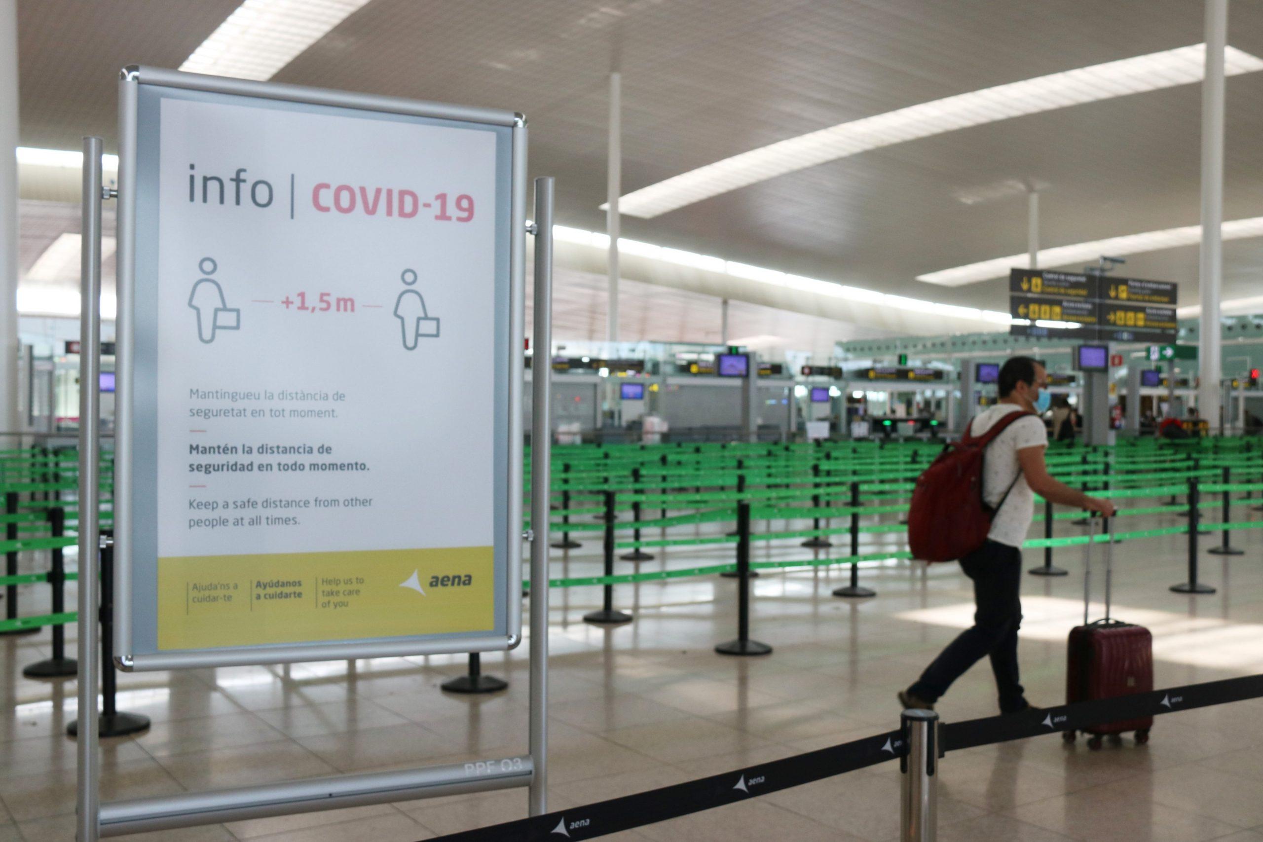 Un cartell informatiu de la covid-19 i un passatger arrossegant una maleta amb el control de seguretat de la T1 de l'Aeroport del Prat pràcticament buit | ACN