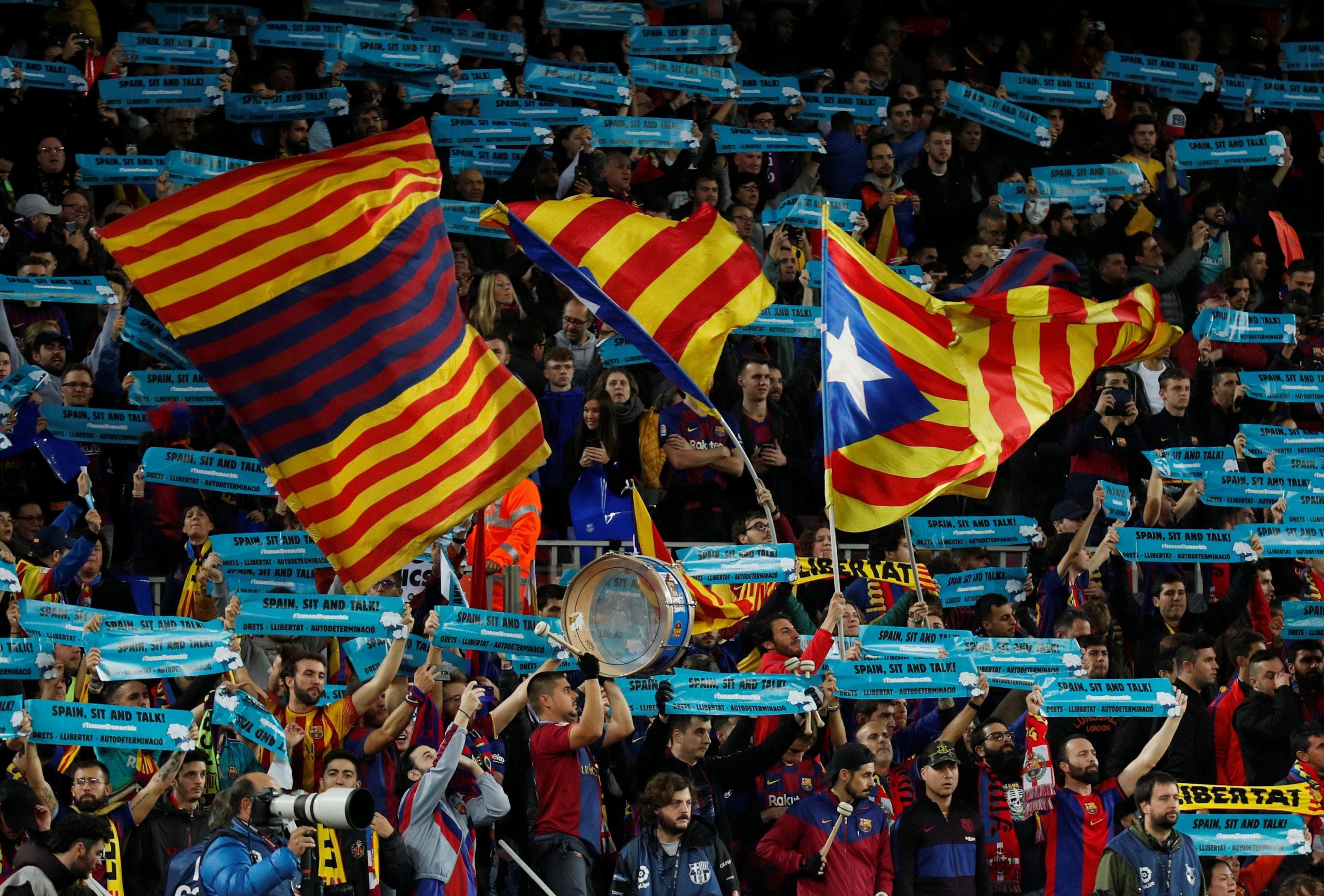 Cartells amb el lema 'Spain, sit and talk' del Tsunami Democràtic a l'inici del clàssic al Camp Nou entre estelades | ACN