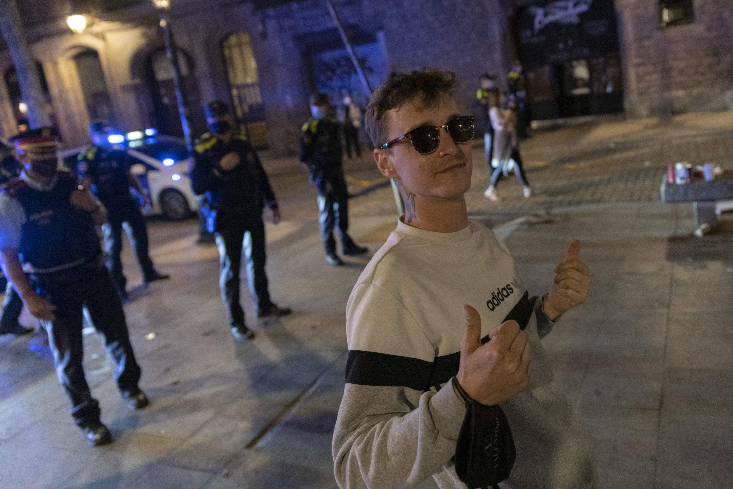 Un jove davant de policies que desallotjaven una aglomeració a Barcelona / EP