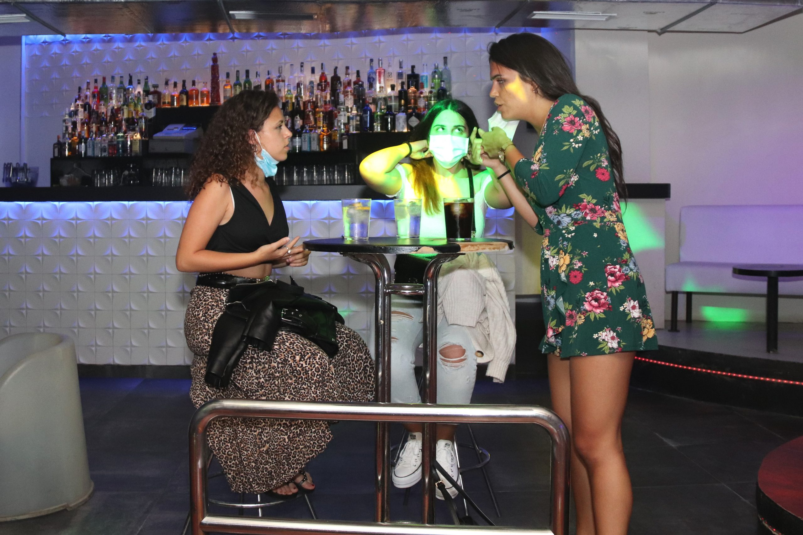 Tres clientes de la discoteca Totem fent una copa en una de les taules que s'han col·locat.