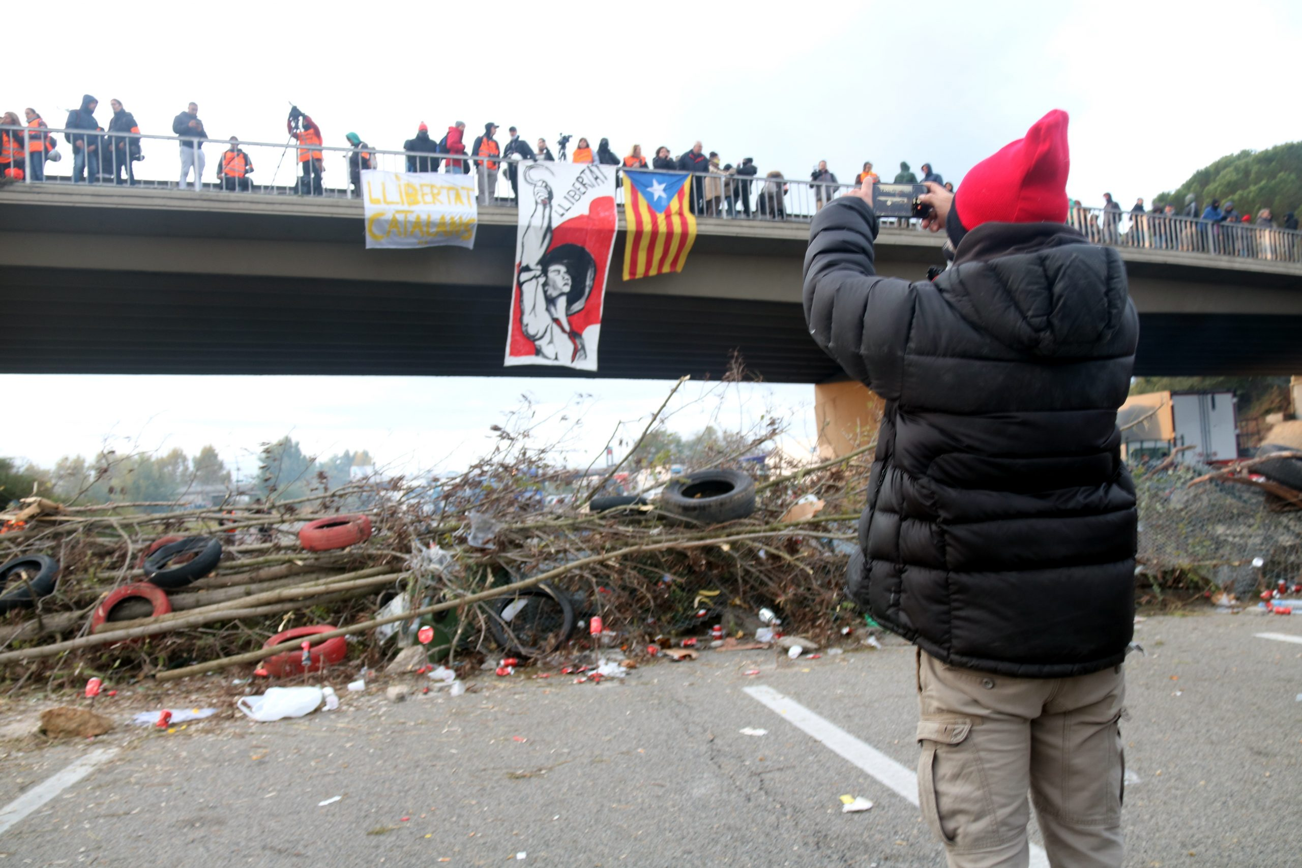 Un home amb barretina fent fotos davant una barricada al tall de l'AP-7 a Salt | ACN