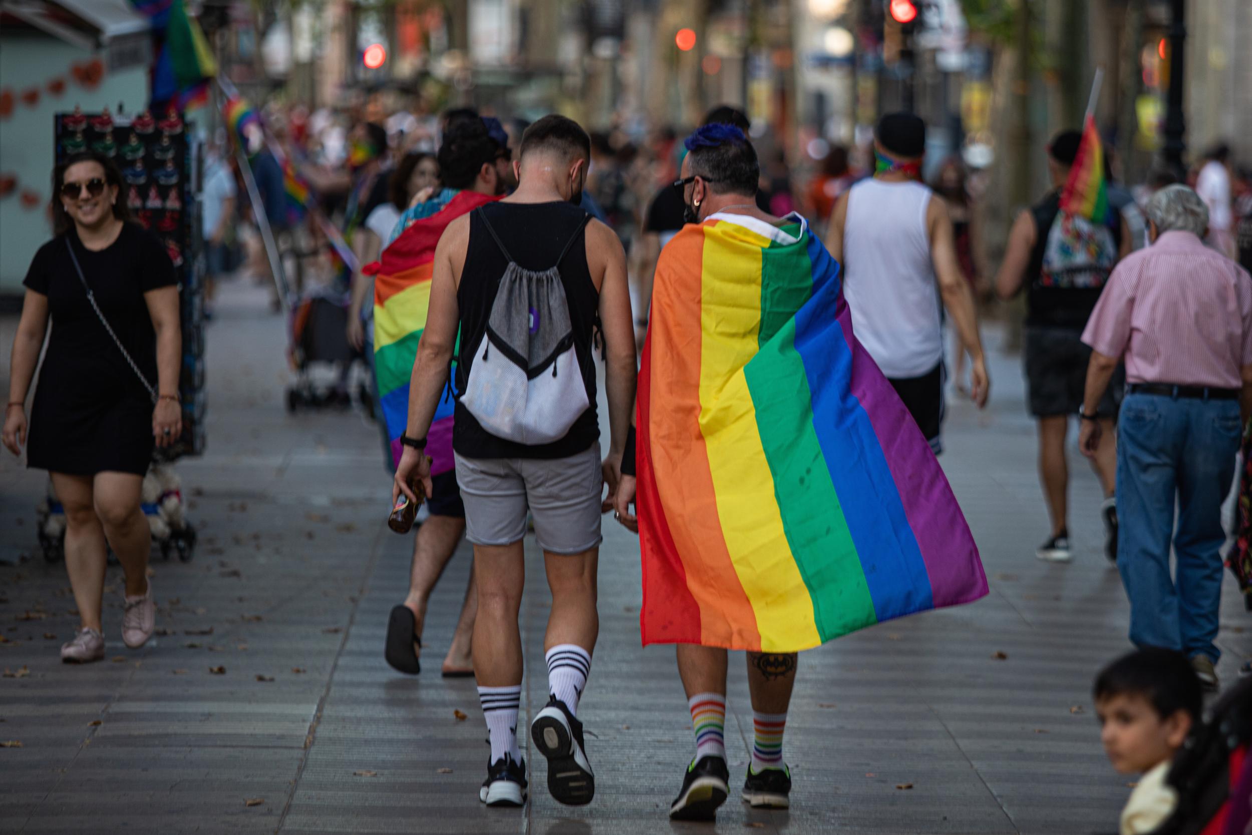 Dos nois amb una bandera LGBTI passegen per Barcelona el dia de l'orgull del 2020 / EP