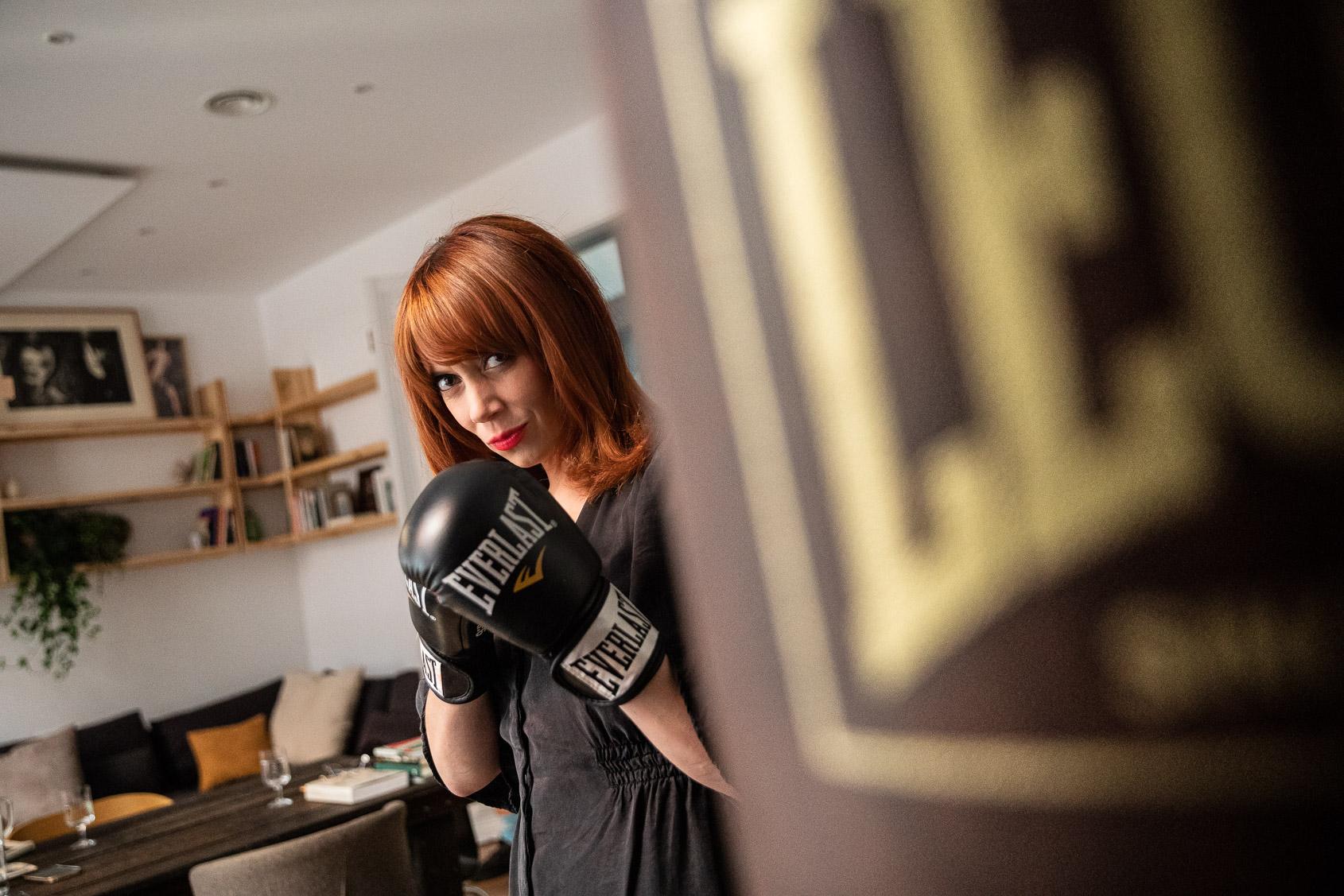 Paula Bonet amb els guants i el sac de boxa que té al costat de les seves pintures | Jordi Borràs