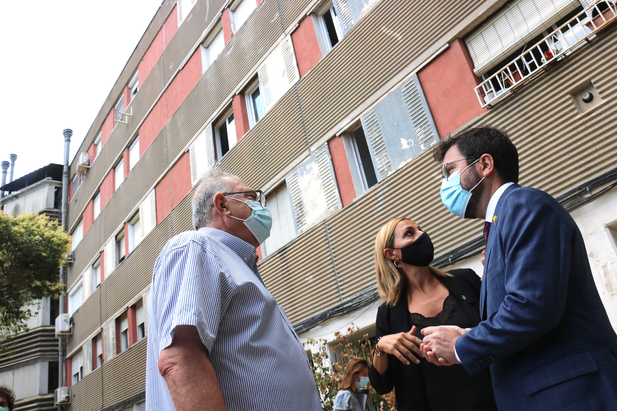 Eel president de la Generalitat, Pere Aragonès, i l'alcaldessa de Badia del Vallès, Eva Menor, amb un veí davant d'un edifici amb amiant / ACN