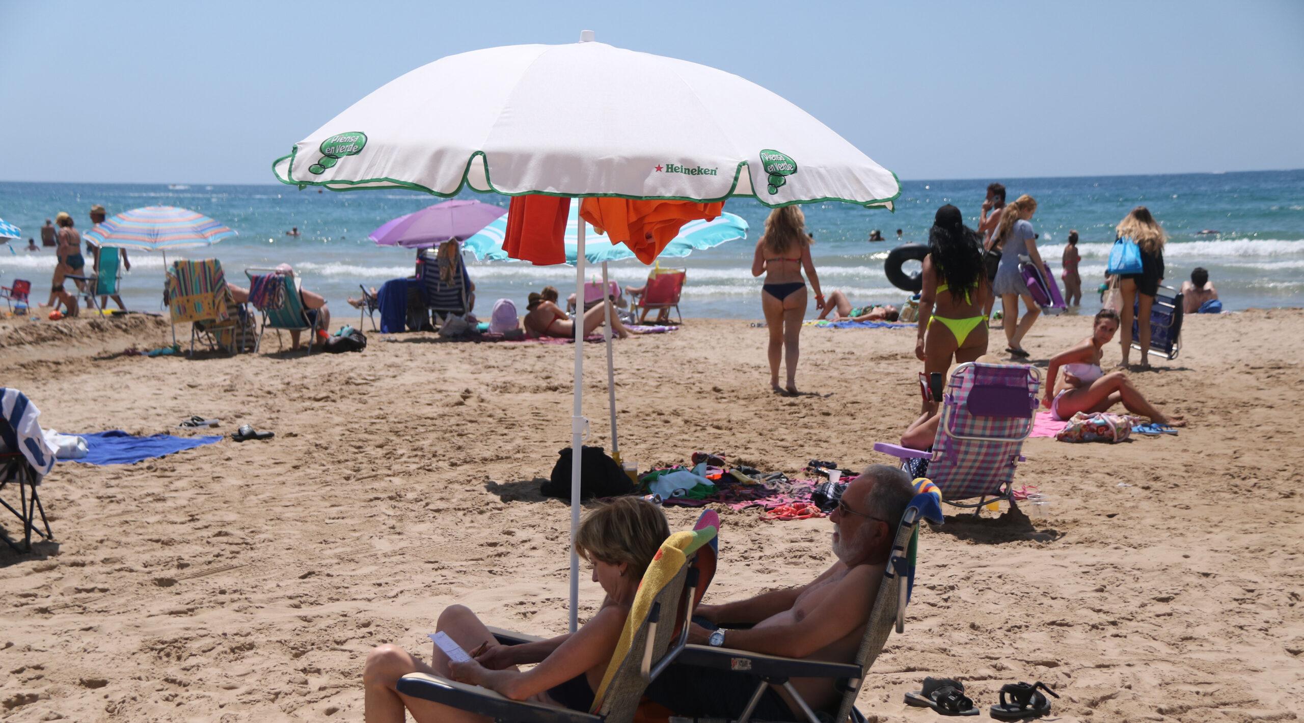 Dues persones sota un para-sol a la platja de Salou. Foto del 6 de juliol de 2021 / ACN
