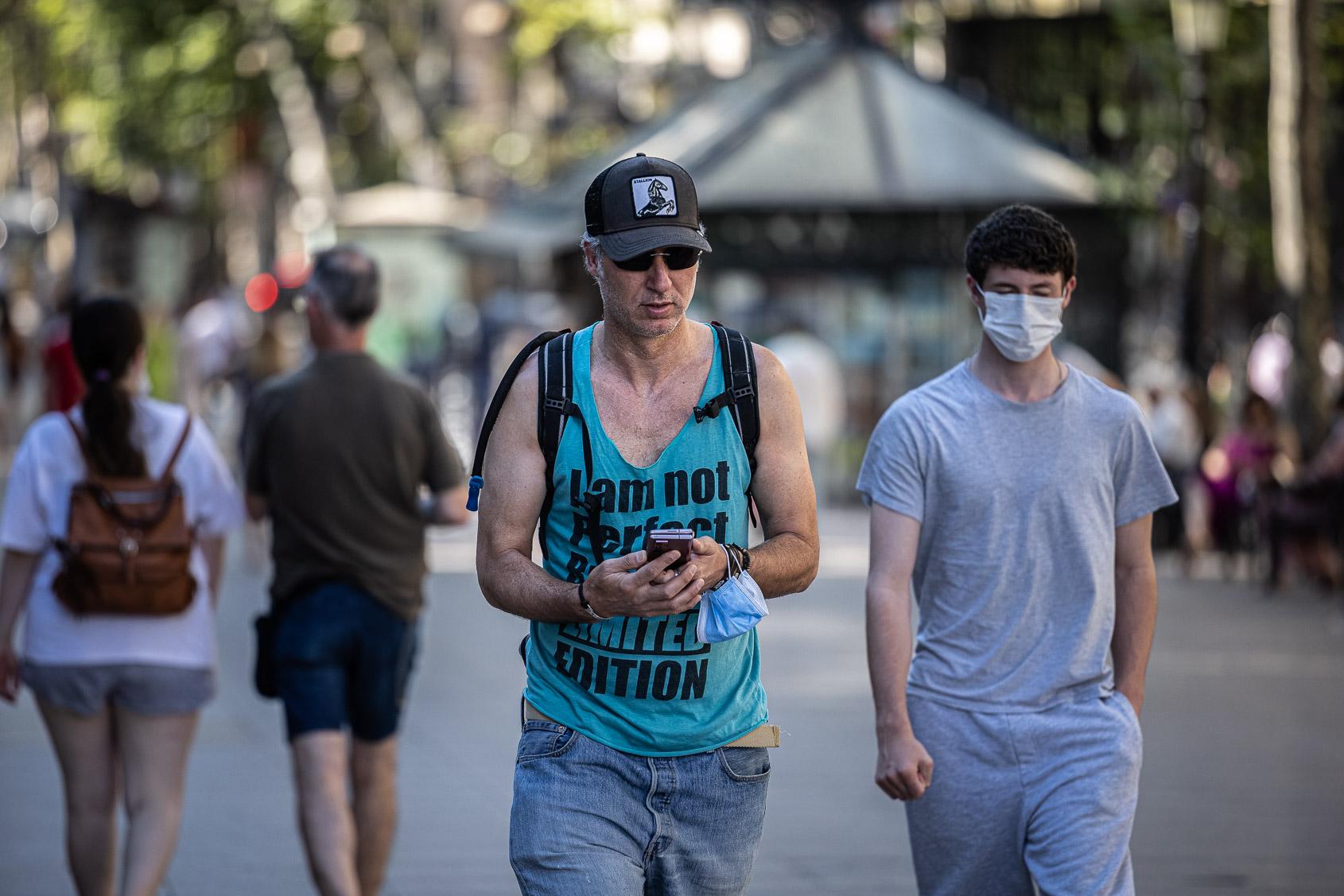 Un vianant sense mascareta i un altre amb mascareta a la Rambla, a Barcelona, en plena cinquena onada, el juliol del 2021 / Jordi Borràs