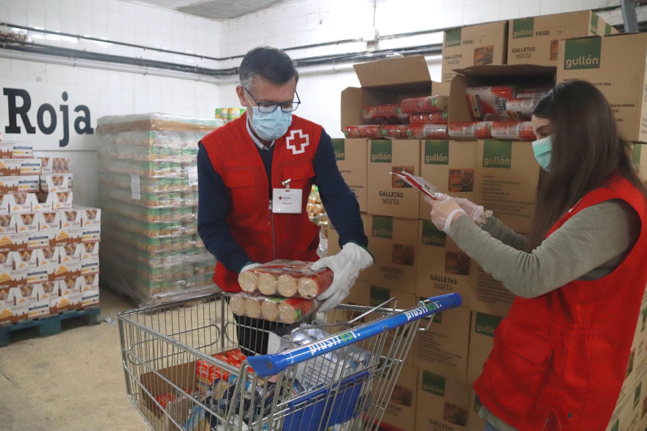 Dos voluntaris de Creu Roja Tarragona omplint el carro d'aliments per una persona en situació de vulnerabilitat / ACN