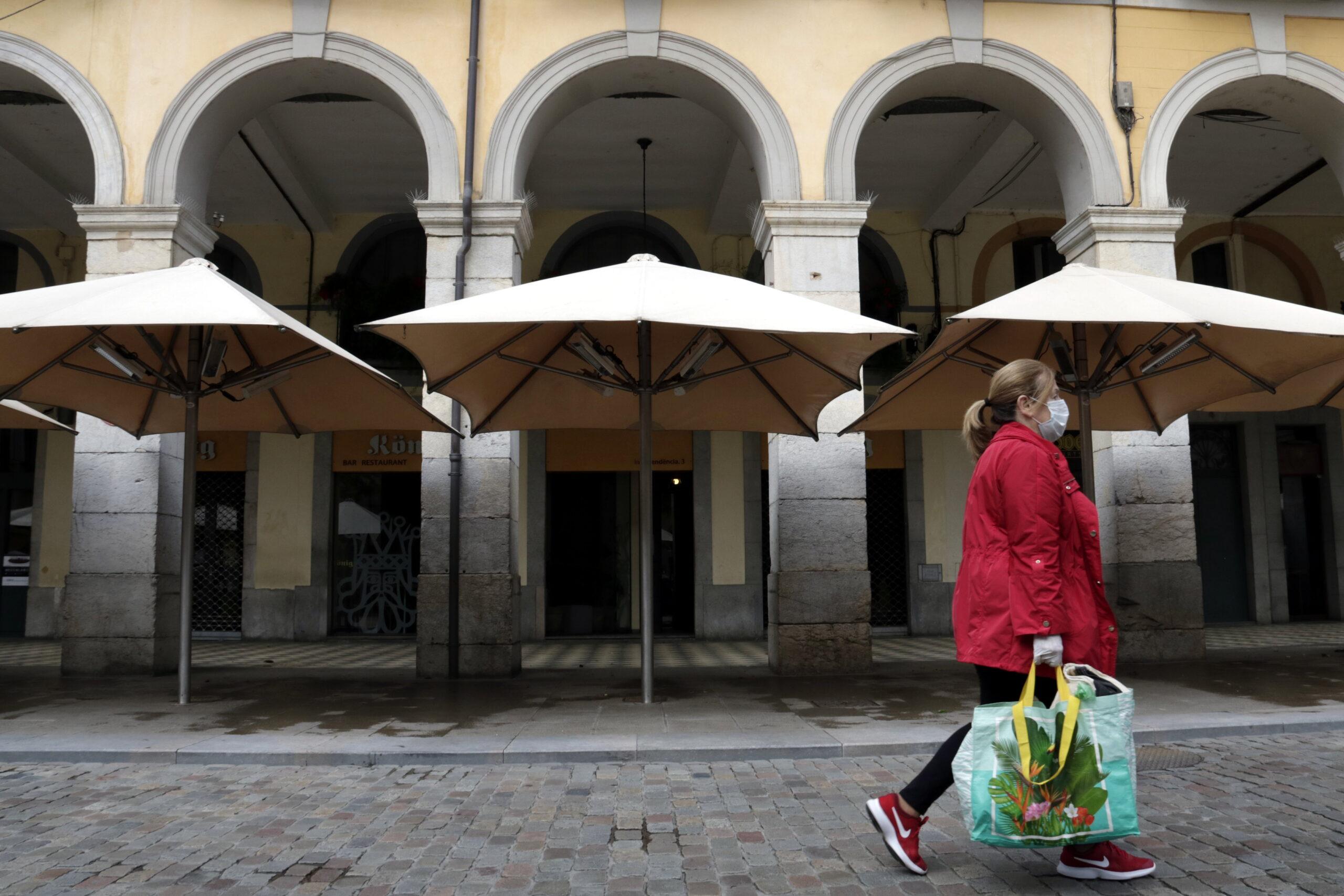 Una dona amb mascareta passa per davant de les terrasses buides i els restaurants tancats / ACN