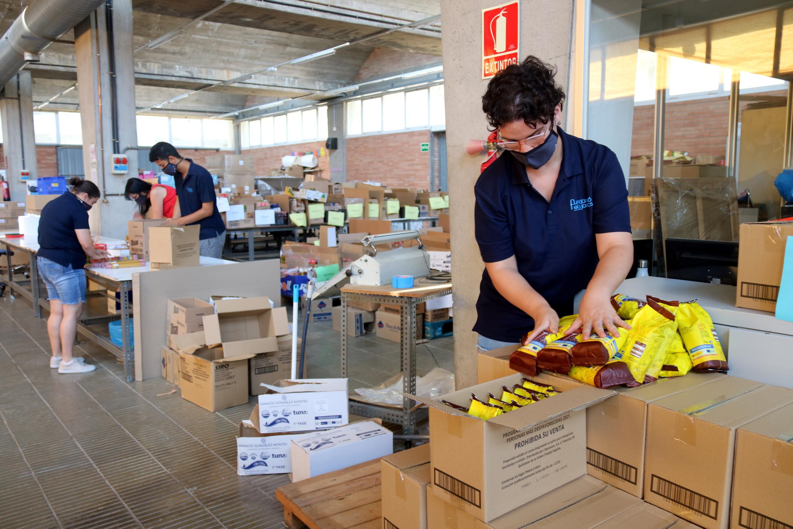 Usuaris del centre ocupacional de la Fundació Els Joncs preparant els lots de menjar | ACN