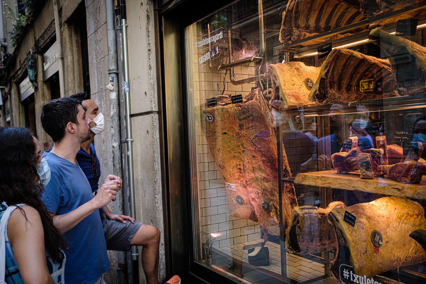 Un grup de gent a la porta d'una carnisseria a Barcelona /Jordi Borràs