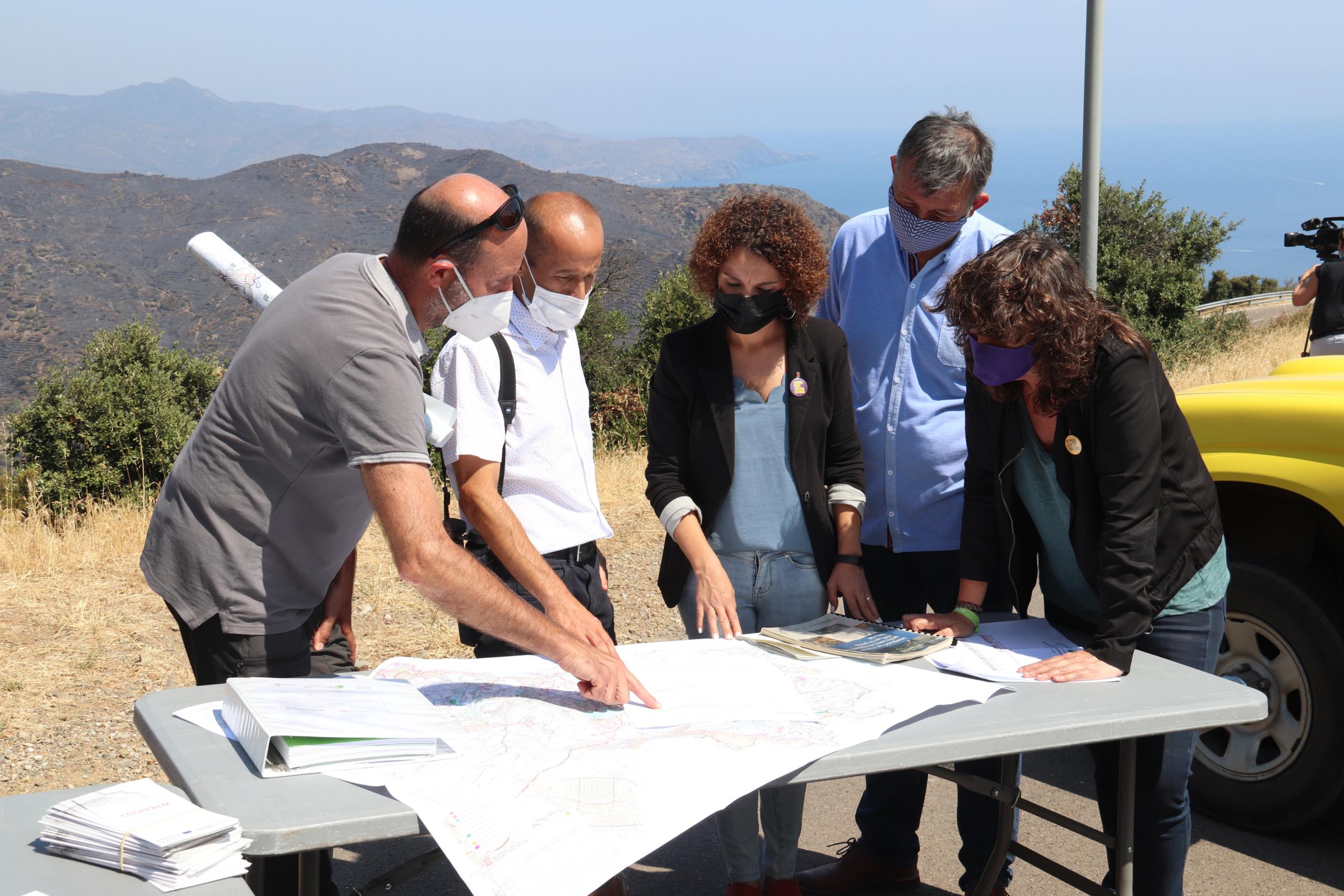 La consellera d'Acció Climàtica, Teresa Jordà, escoltant l'afectació de l'incendi del Cap de Creus amb les muntanyes de fons cremades el 21 de juliol de 2021 (ACN)