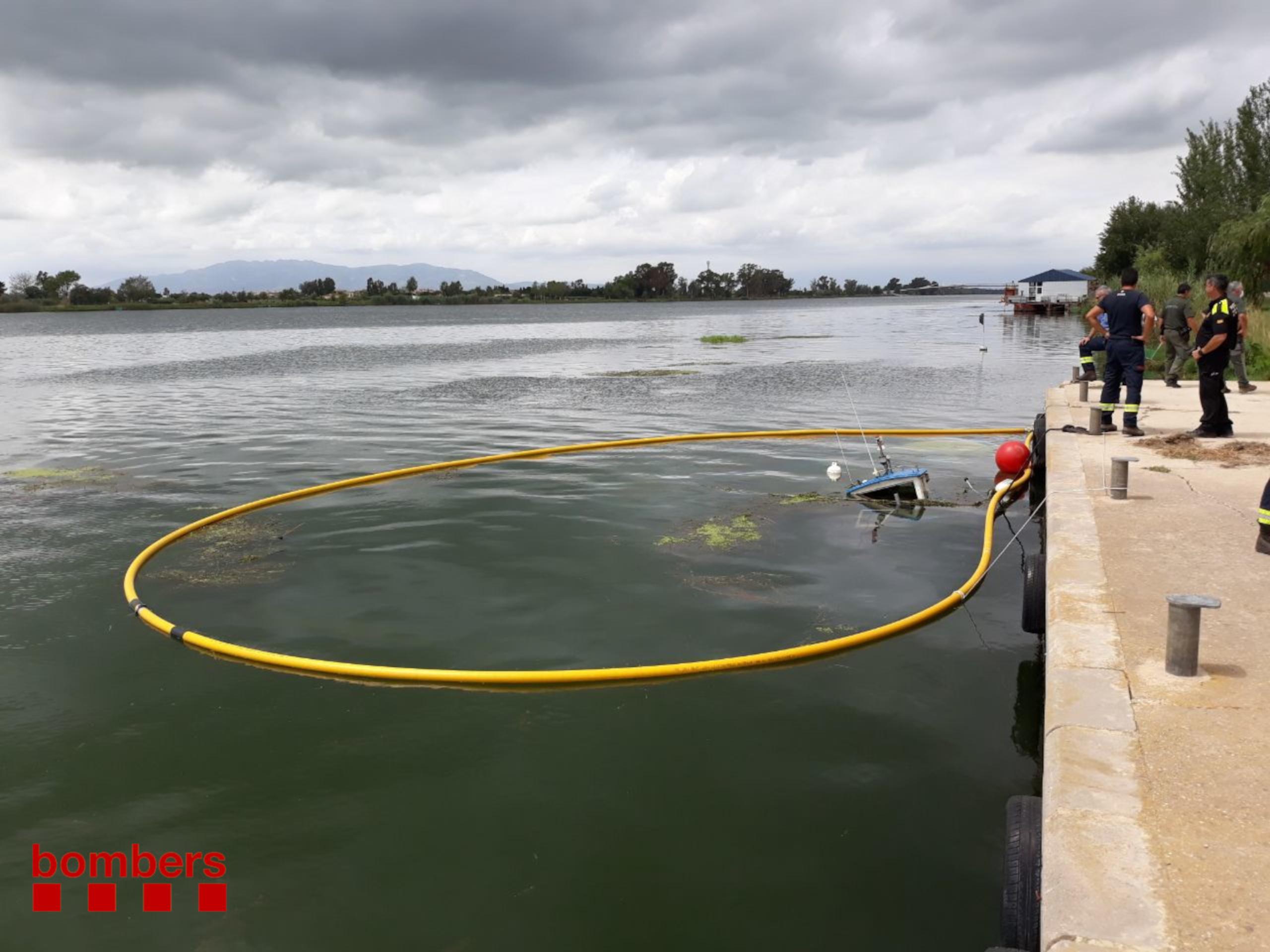 La mànega amb què els Bombers contenen la fuga de gasoil que ha provocat al riu Ebre l'enfonsament d'un vaixell pesquer a Deltebre (ACN)