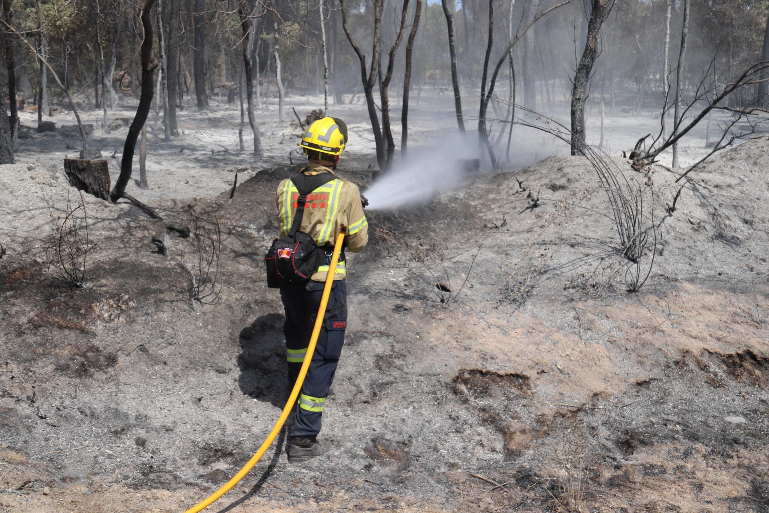 Un bomber remullant una de les zones cremades a l'incendi de Ventalló aquest diumenge 25 de juliol de 2021 / ACN