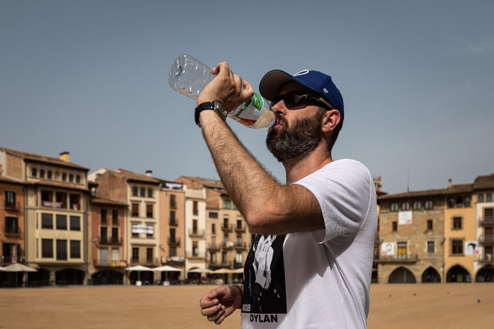 Un vianant beu aigua a la plaça Major de Vic, deserta en plena onada de calor / Jordi Borràs