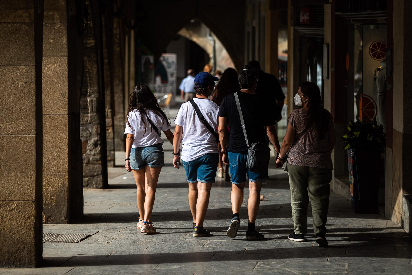 Vianants sota les voltes de la plaça Major de Vic, única zona amb ombra, en plena onada de calor / Jordi Borràs