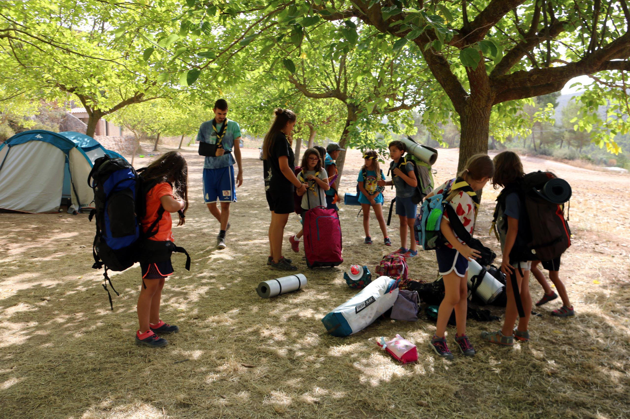 El grup dels Castors i les Llúdrigues de l'Agrupament Escolta i Guia Verge de la Candela, amb les motxilles, abans de marxar del campament de Sant Martí de Tous (ACN)