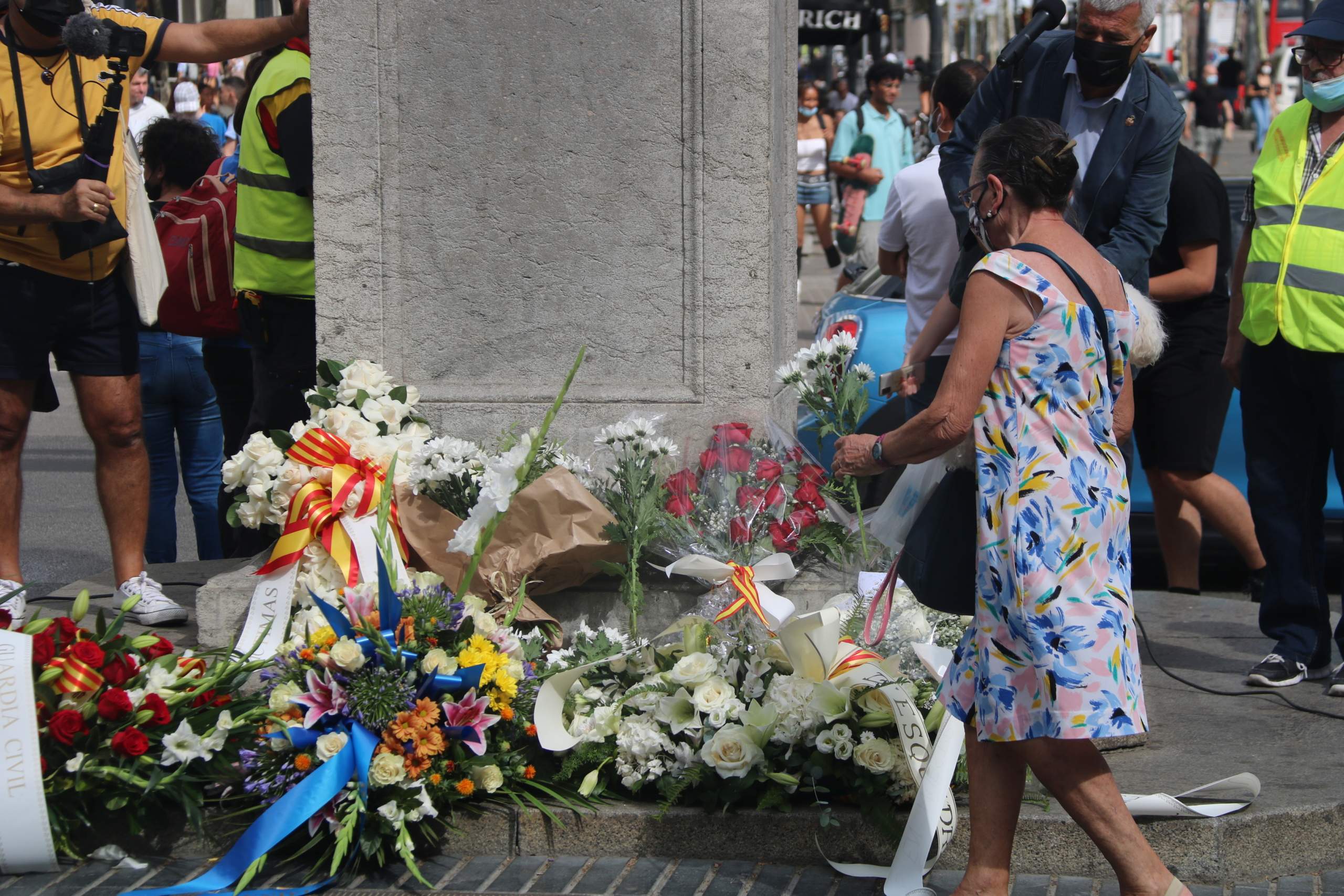 Una dona dipositant una flor a l'ofrena organitzada per l'Associació Catalana de Víctimes d'Organitzacions Terroristes en record a les víctimes del 17-A / ACN