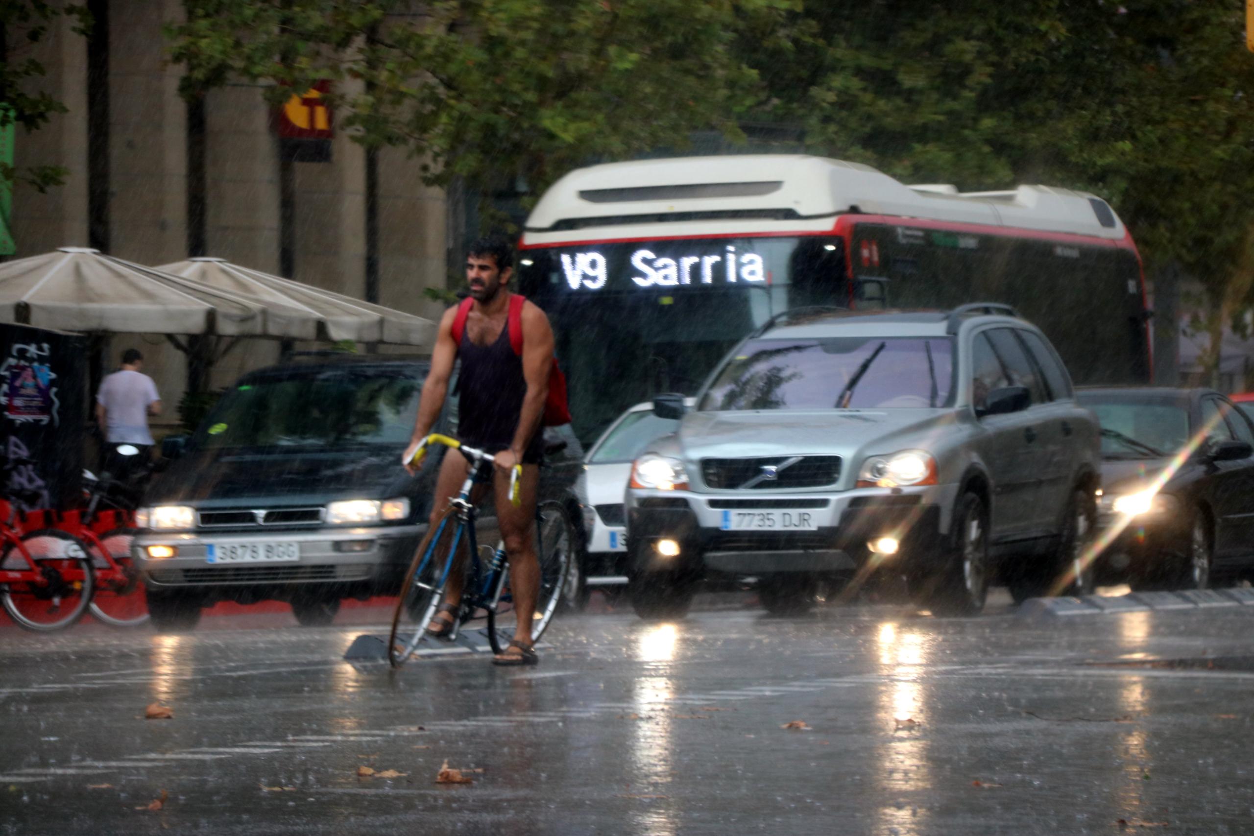 Un ciclista i diversos turismes sota la pluja a l'Avinguda Paral·lel de Barcelona | ACN